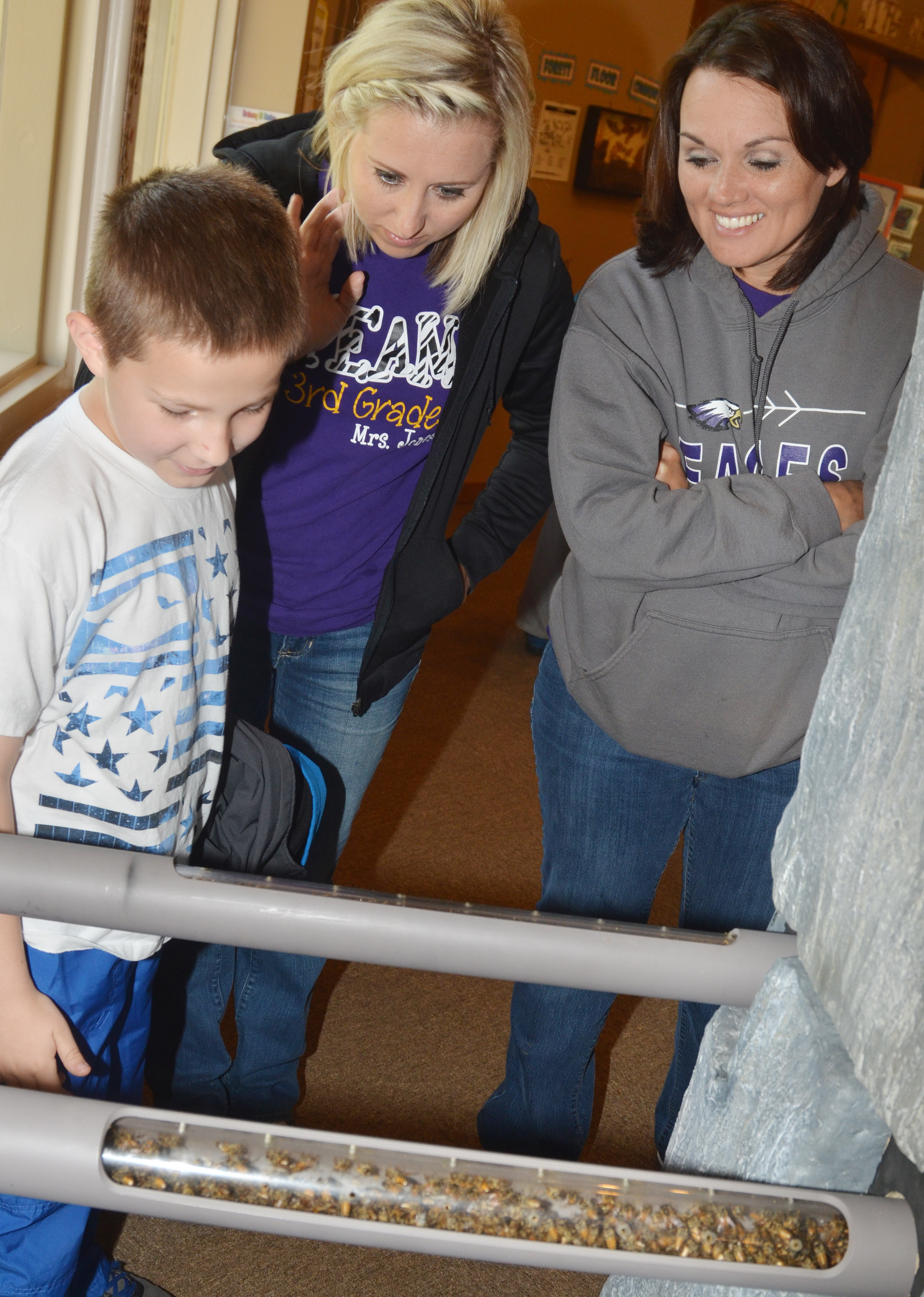 CES third-grader Grayson Dooley looks at the bee hive at the Green River Lake Visitor Center, with his teacher Hannah Jones, center, and third-grade assistant Melissa Pratt.