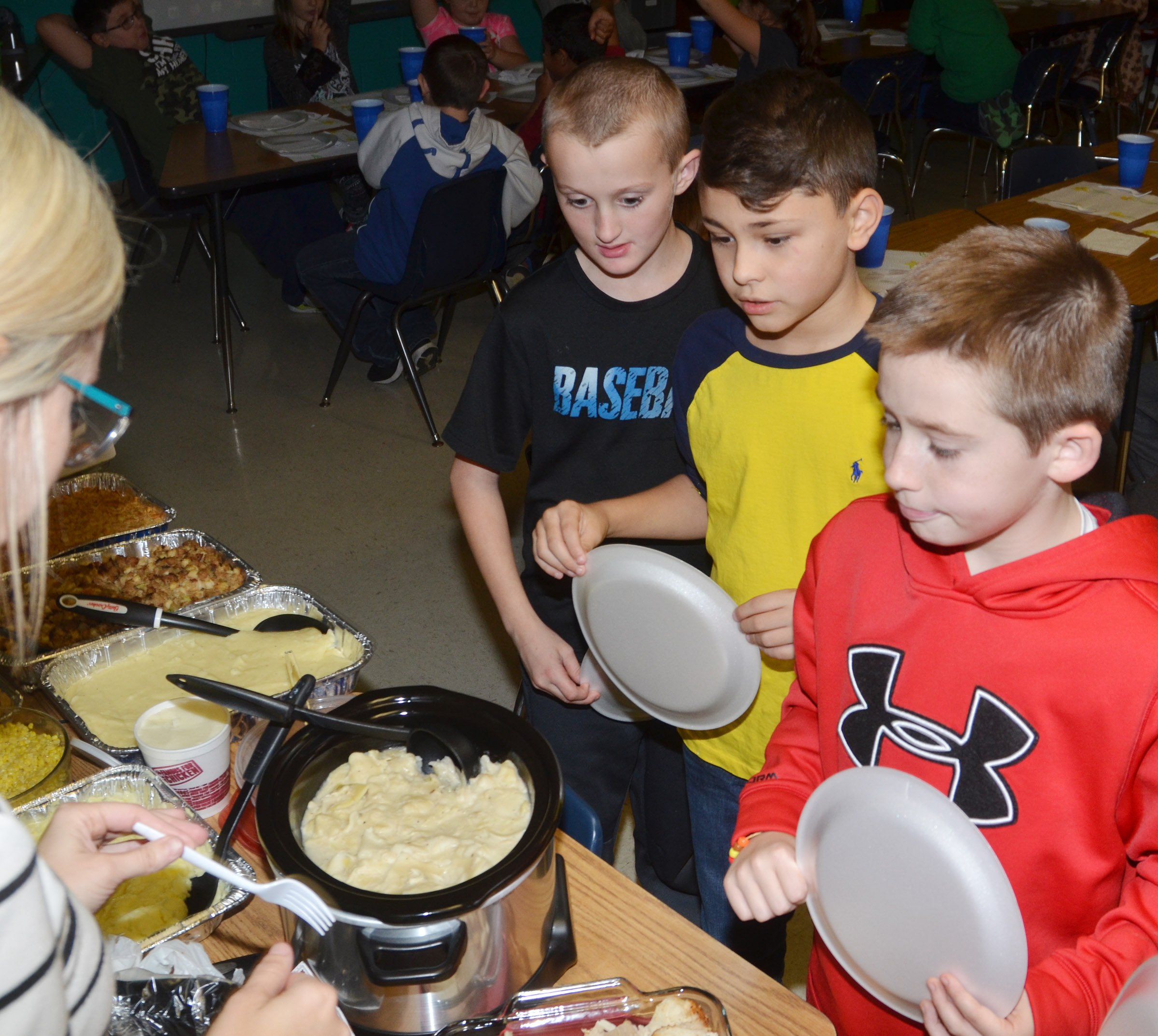 CES third-grade teacher Hannah Jones serves, from left, Zachary Cox, Braygon Noegel and Lanigan Price.