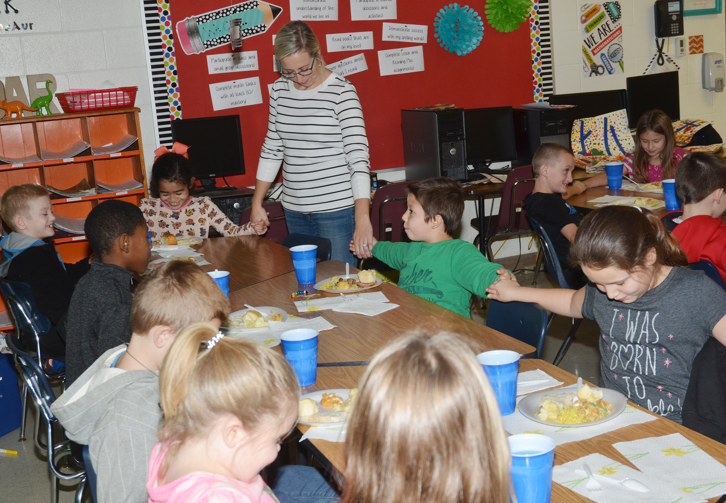 CES third-grade teacher Hannah Jones and her students pray together before enjoying their Thanksgiving feast.