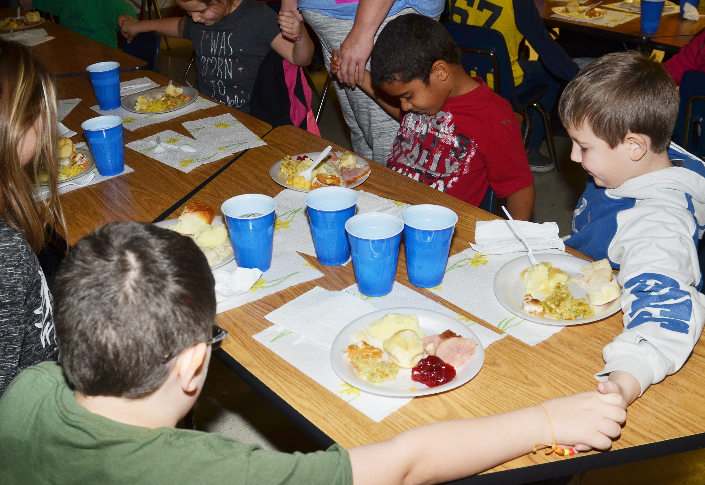 CES third-graders in Hannah Jones's class pray together before enjoying their Thanksgiving feast.