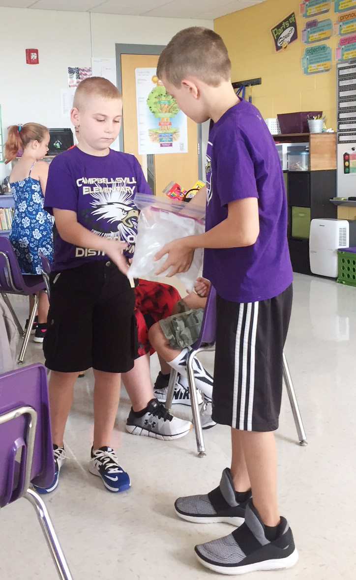 CES third-graders Joseph Greer, at left, and Aidan Wilson work together to make ice cream.
