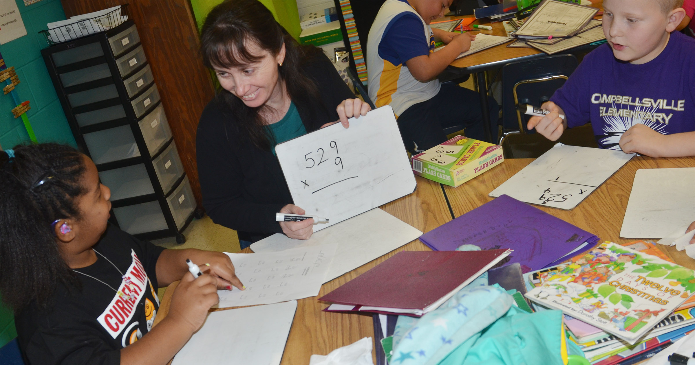 CES Instructional Assistant Andrea Menes helps third-graders KaMiya Williams, at left, and Isaiah Jeffries with a multiplication problem.