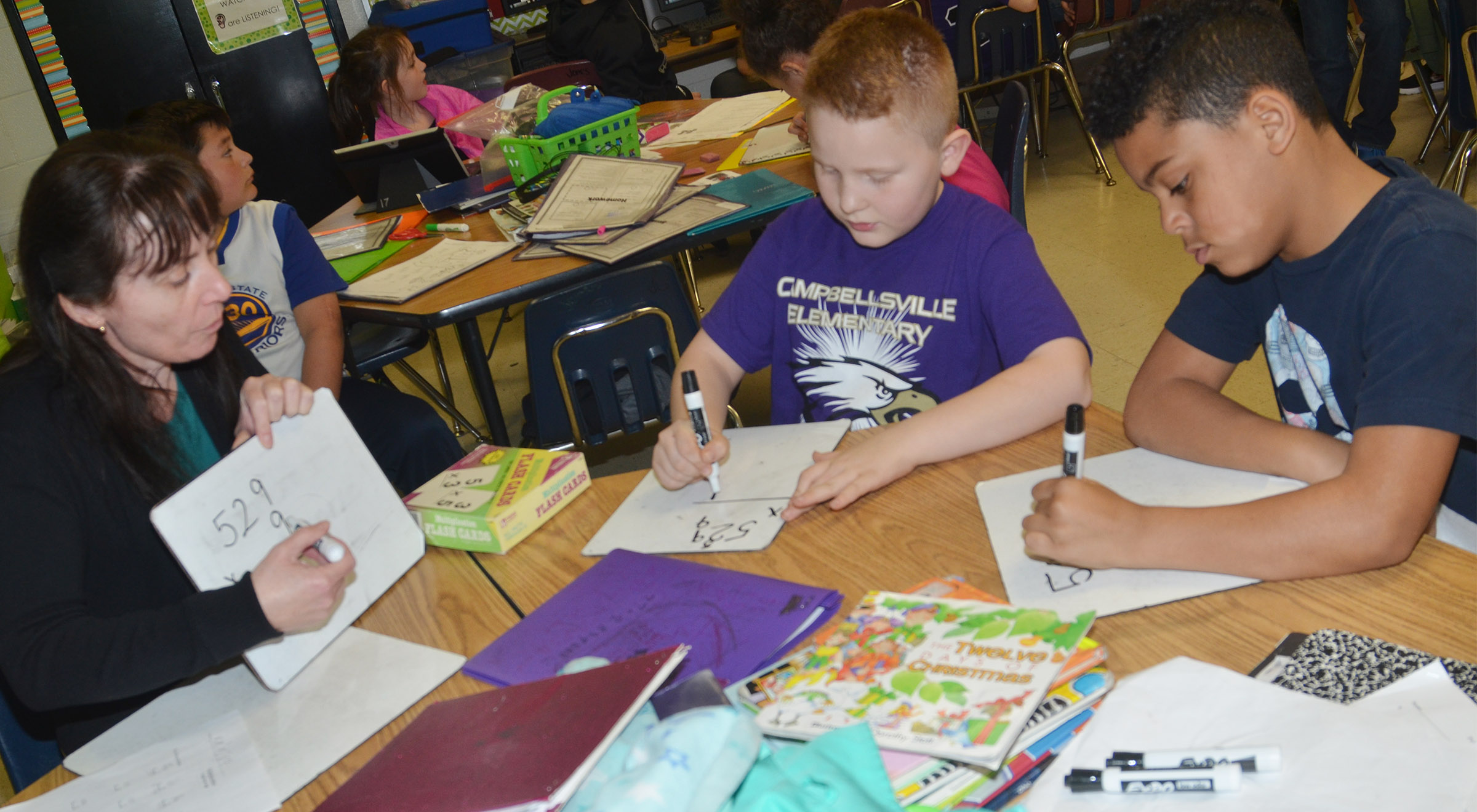 CES Instructional Assistant Andrea Menes helps third-graders Isaiah Jeffries, center, and Bryson Groves work a multiplication problem.