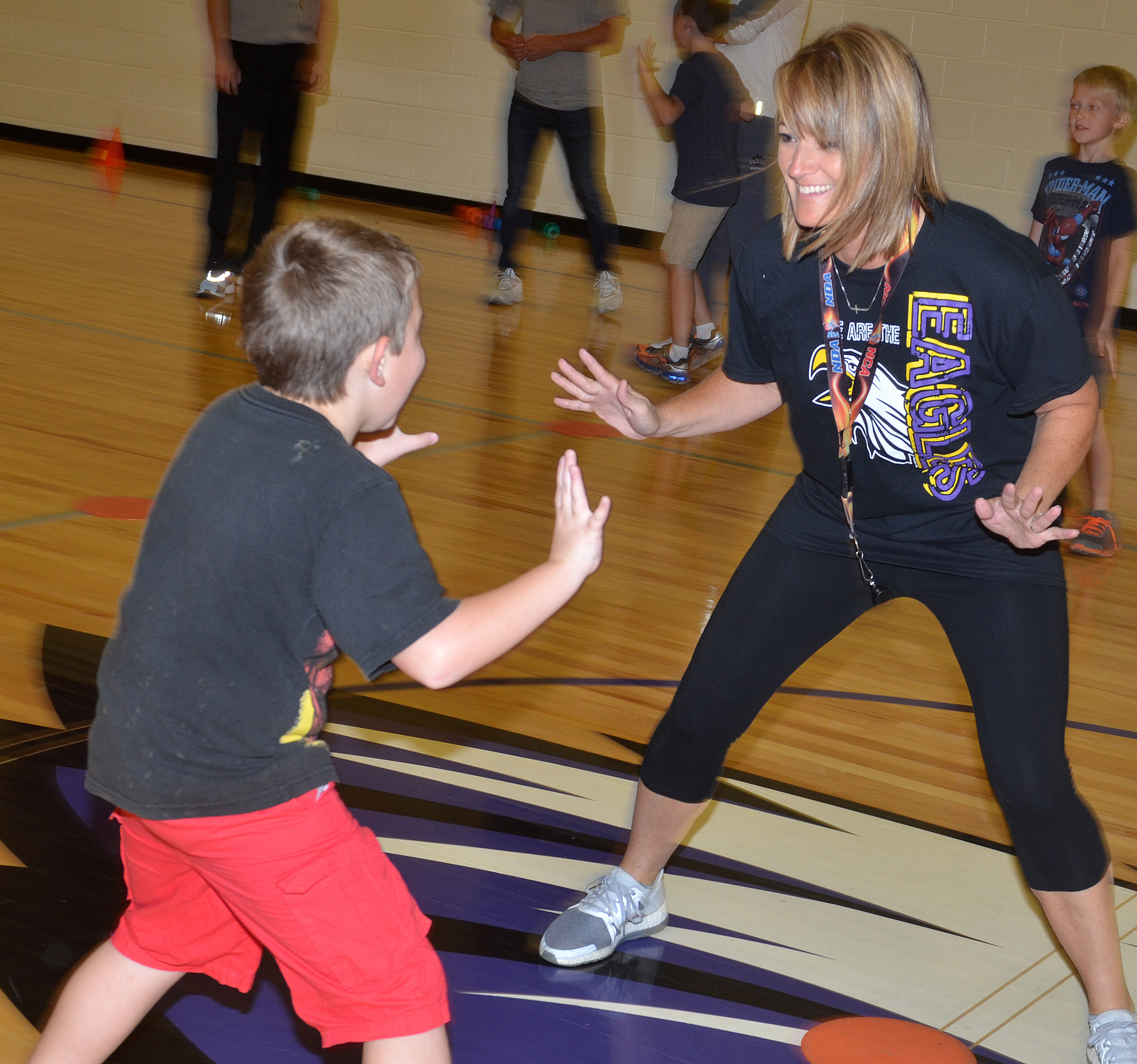 CES physical education teacher Vanessa Adkins runs with third-grader Seamus Huber.