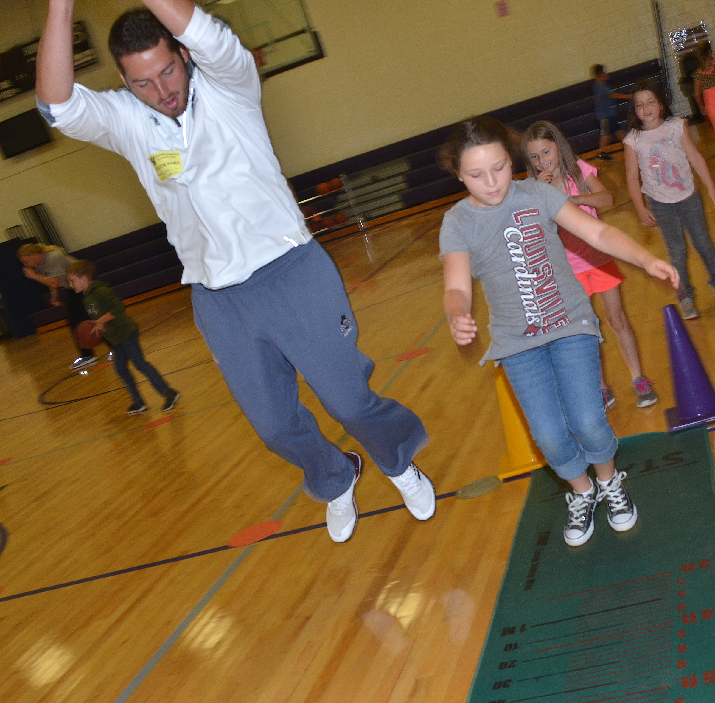 CES third-grader Keely Rakes jumps with Campbellsville University student Ryan Grattan.