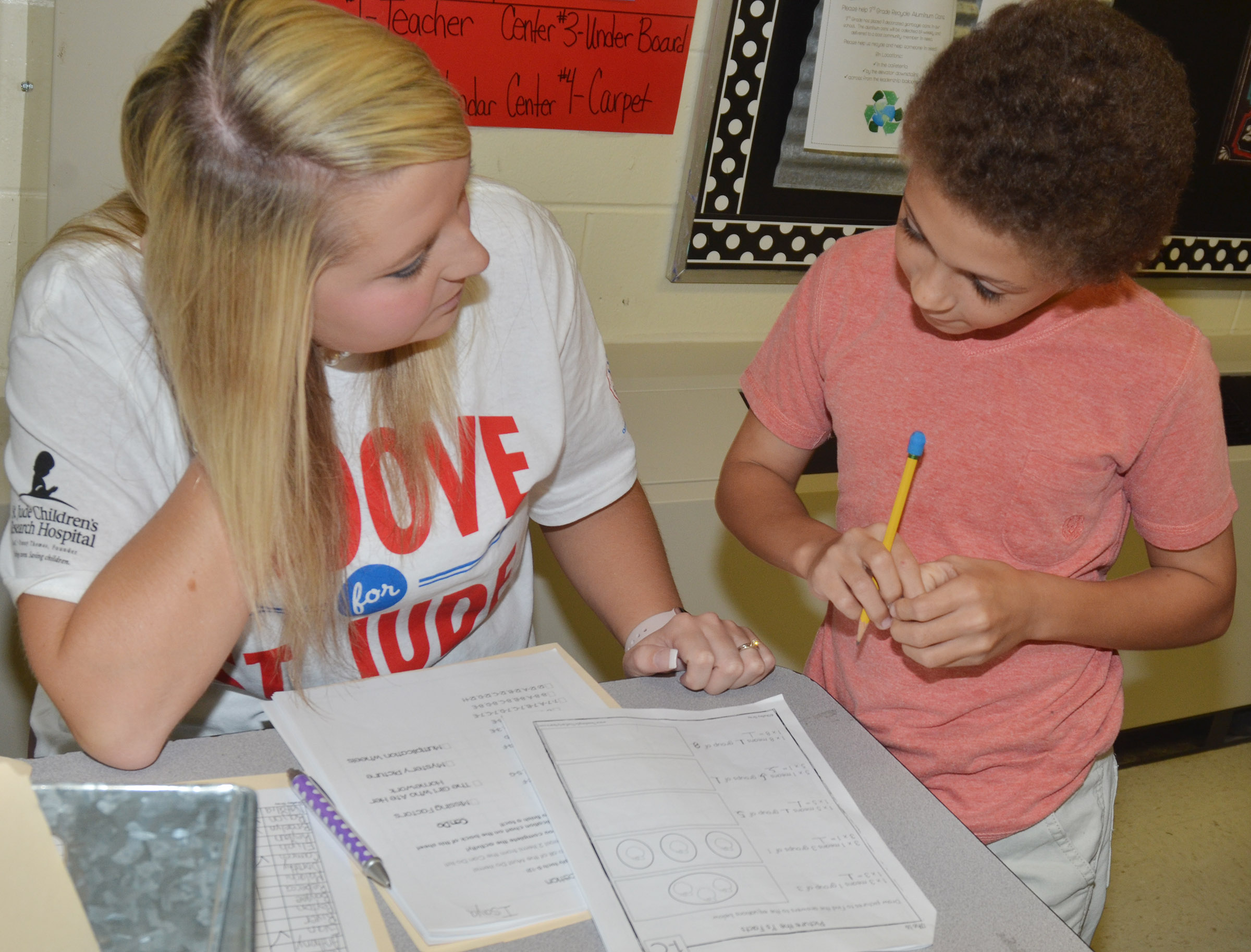 CES third-grade teacher Keri Richard talks to Trever Lasley about his math work.