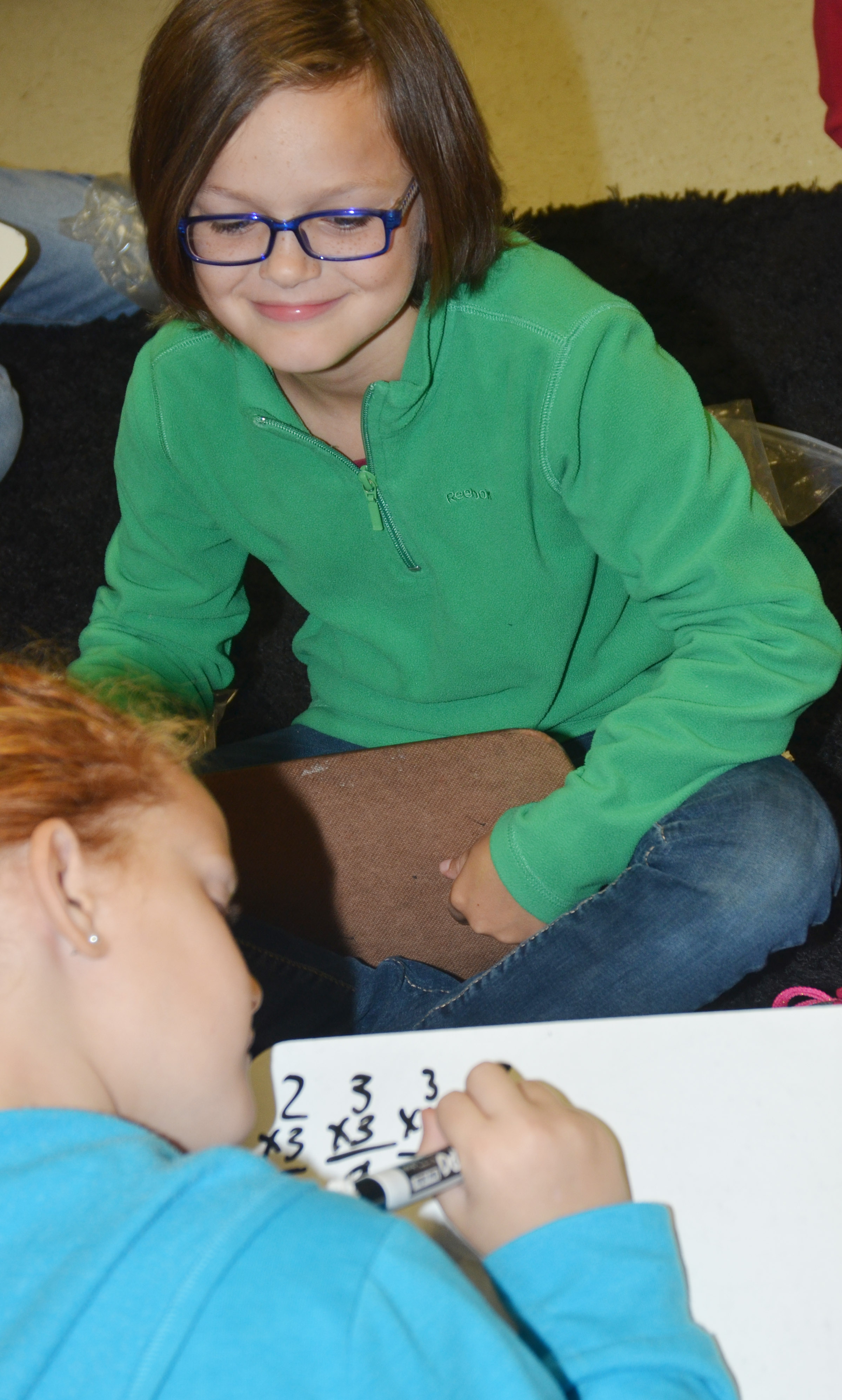 CES third-grader KayLee Lamer smiles as she works with classmate Analeigh Foster to answer a multiplication problem.