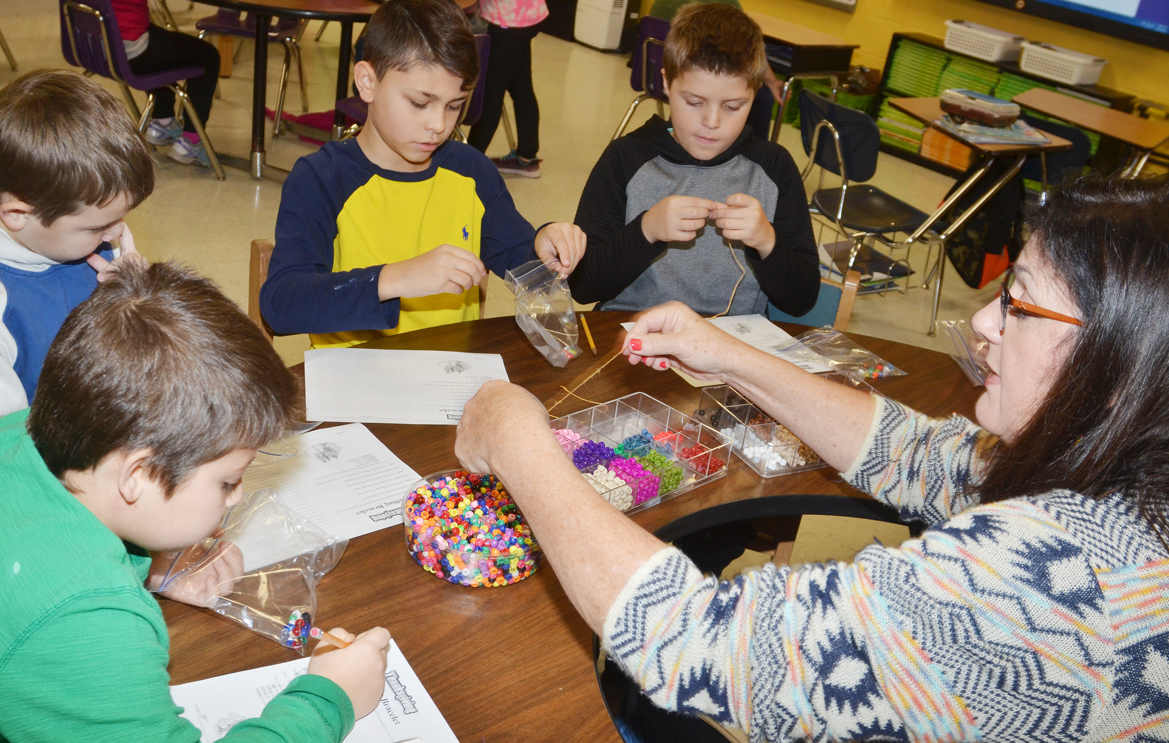 CES third-grade teacher Patty Haley helps students, from left, Dre'mareon Gurley, Seamus Huber, Braygon Noegel and Emerson Gowin make their Thanksgiving bracelets.