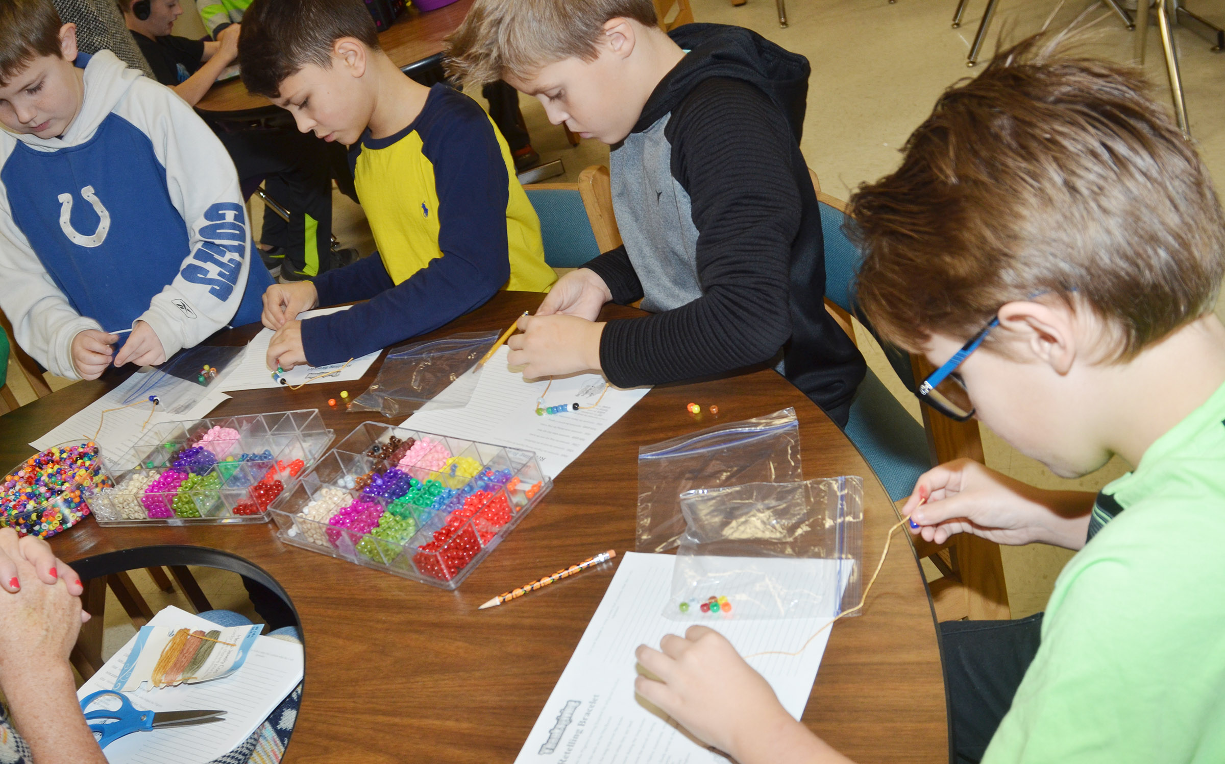 From left, CES third-graders Seamus Huber, Braygon Noegel, Emerson Gowin and Dalton Shively make their Thanksgiving bracelets.