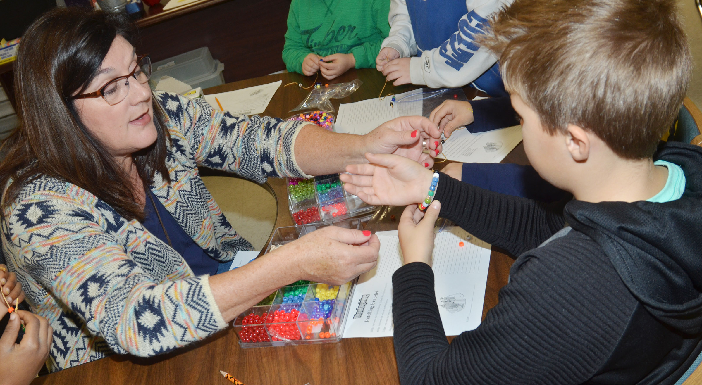 CES third-grade teacher Patty Haley helps Emerson Gowin put on his Thanksgiving bracelet.