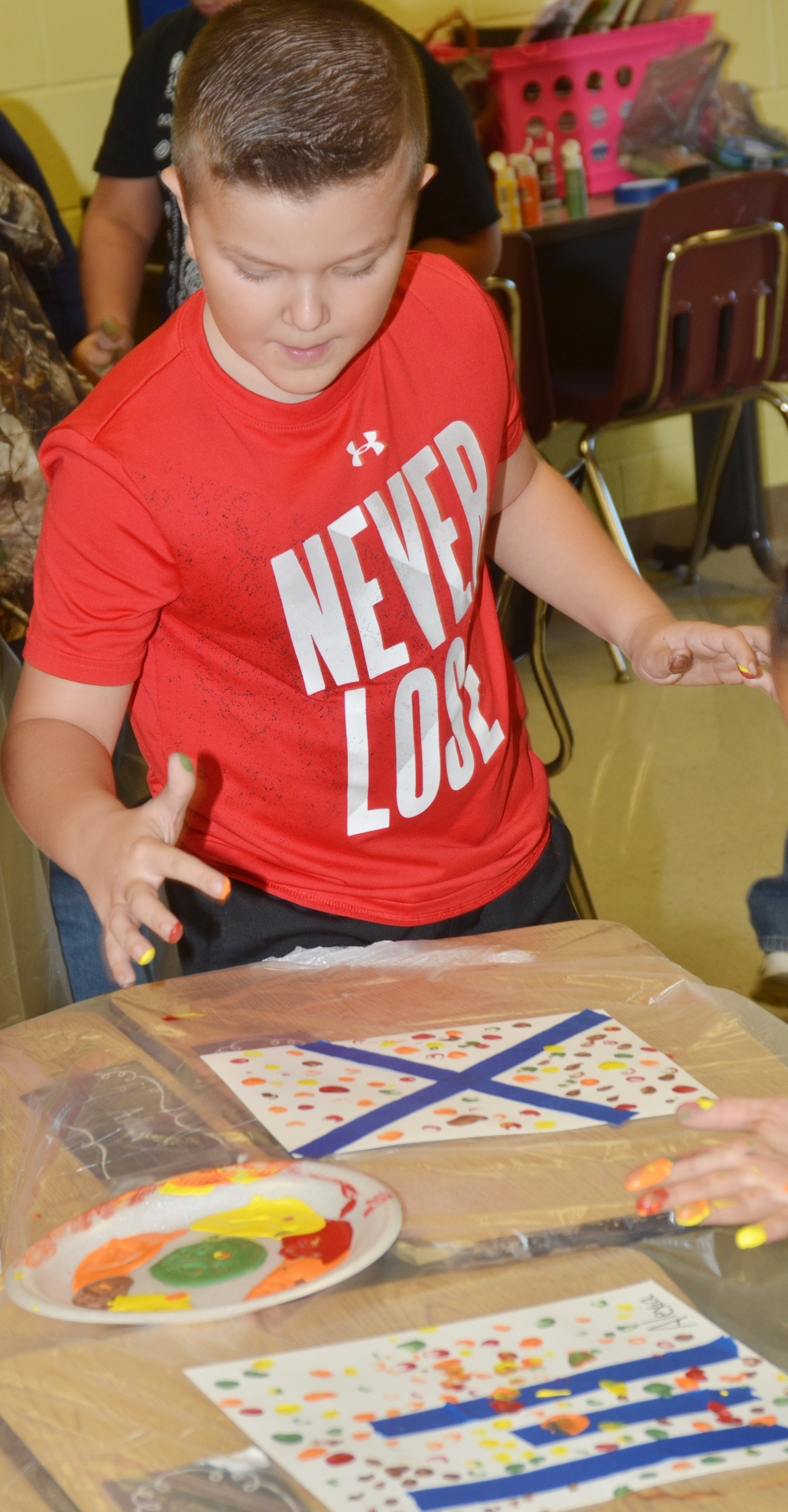 CES third-grader Cayton Lawhorn paints with his fingers.