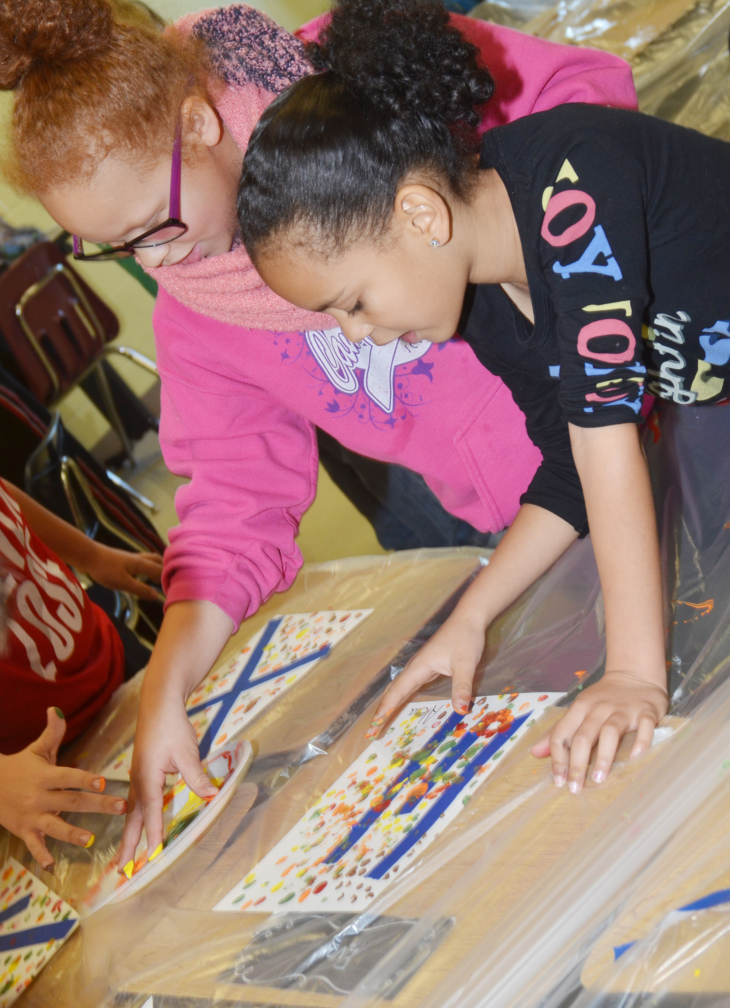 CES third-graders Kallie Taylor, at left, and Alexia Howard paint with their fingers.