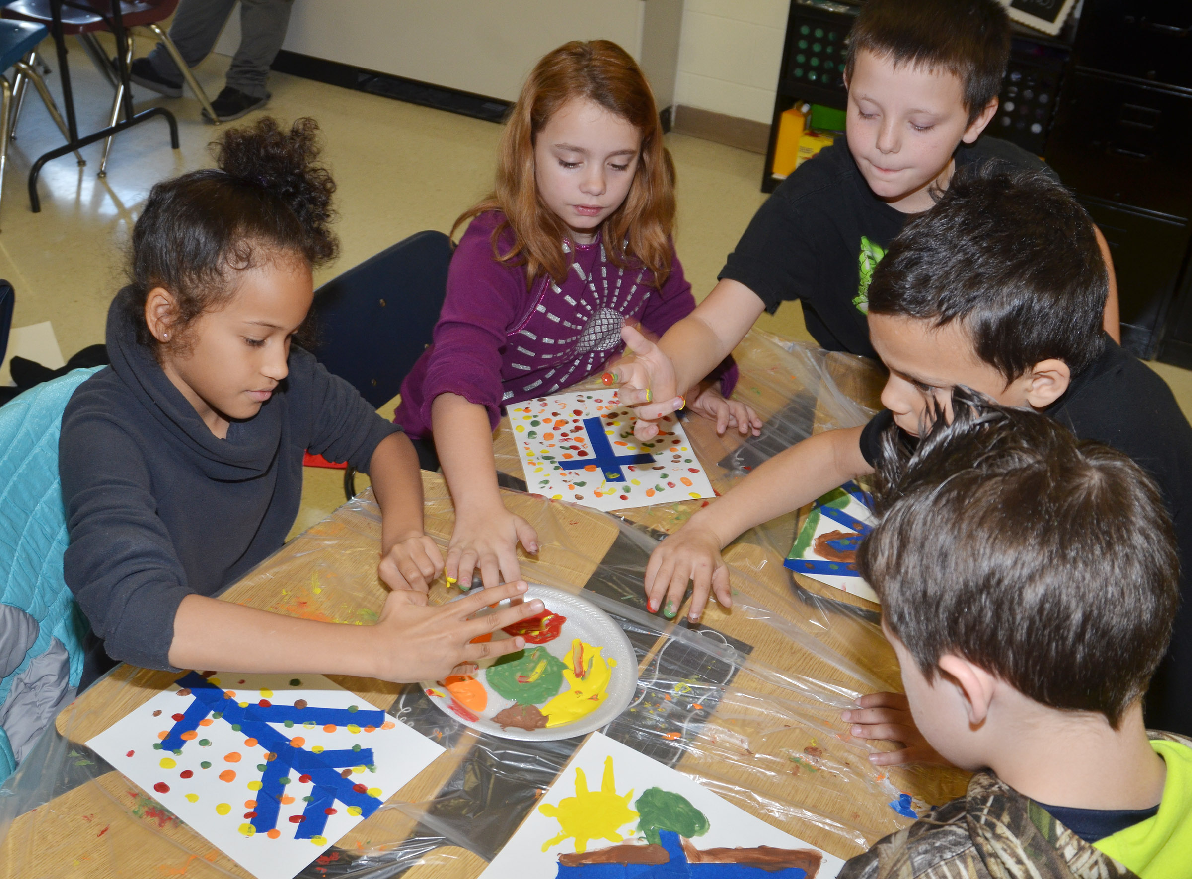 From left, CES third-graders Yazlyn Sutton, Angelina Babbs, Skyler Brown, Donnaven Phillips and Codey Parks paint with their fingers.