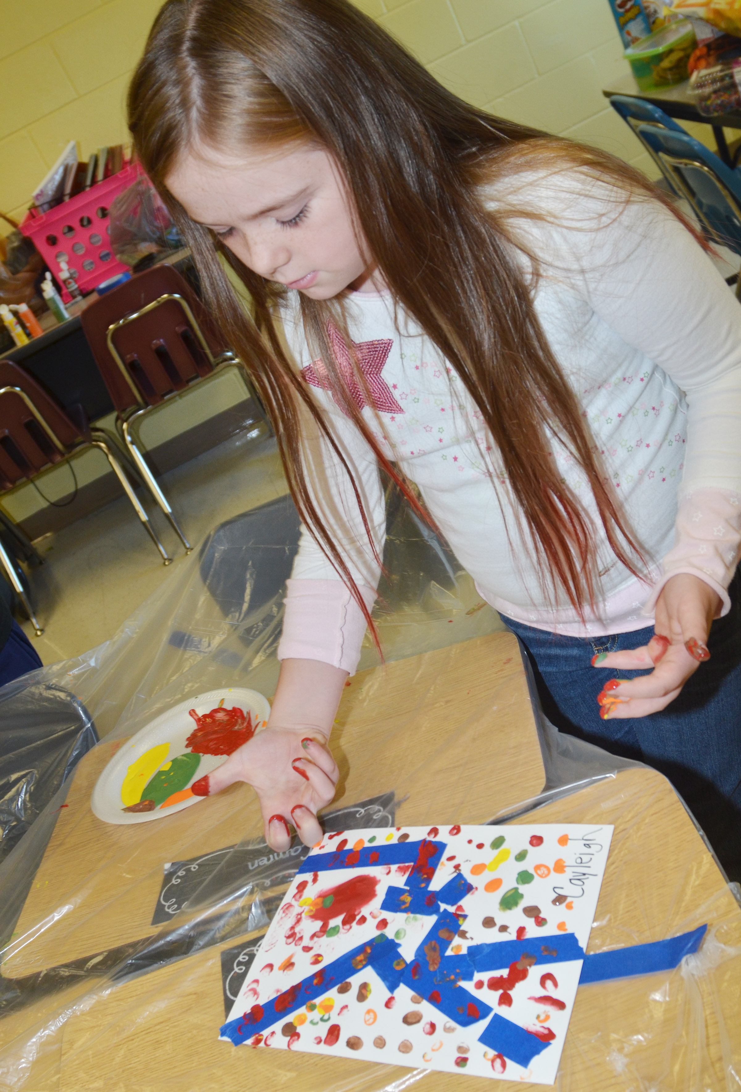 CES third-grader Cayleigh Underwood paints with her fingers.