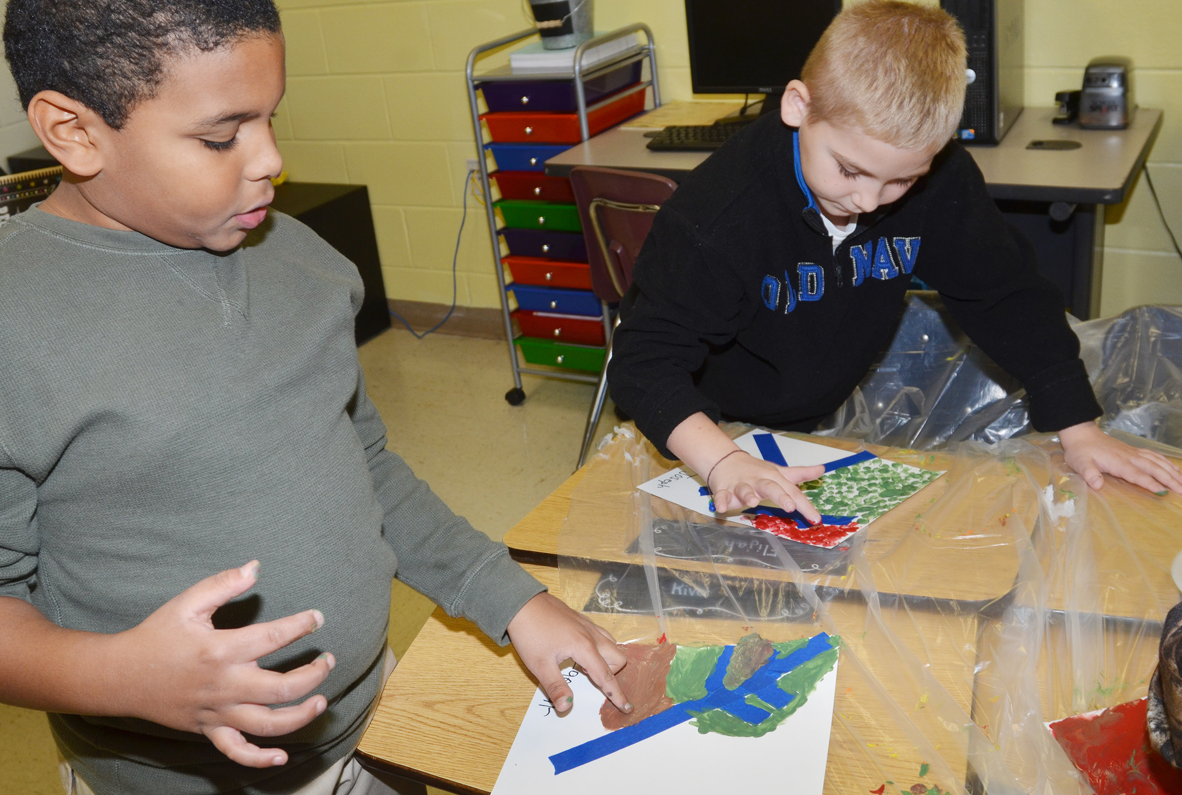 CES third-graders Zaemar Hoskins, at left, and Joseph Greer paint with their fingers.
