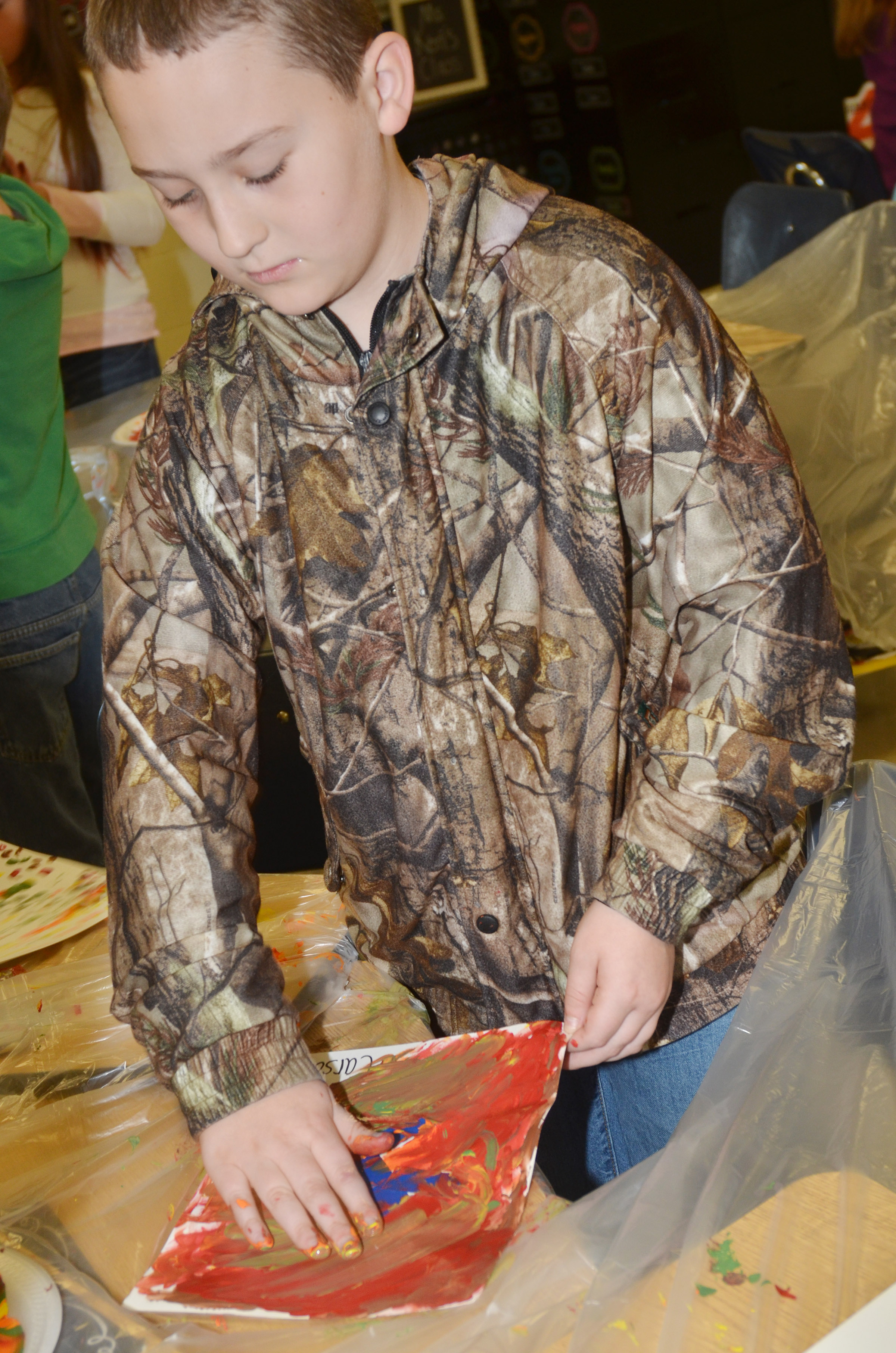 CES third-grader Carson Ford paints with his fingers.