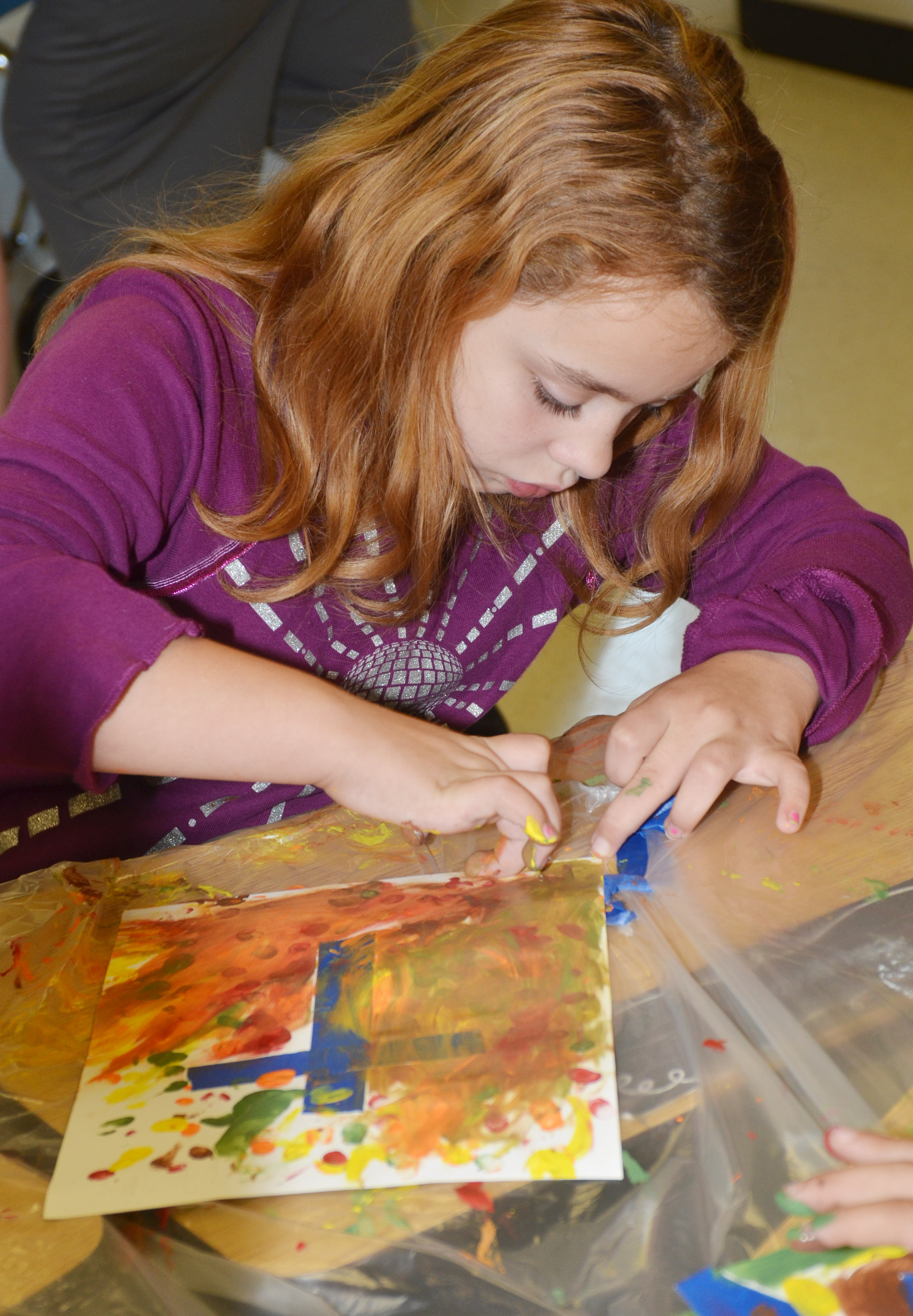 CES third-grader Angelina Babbs paints with her fingers.