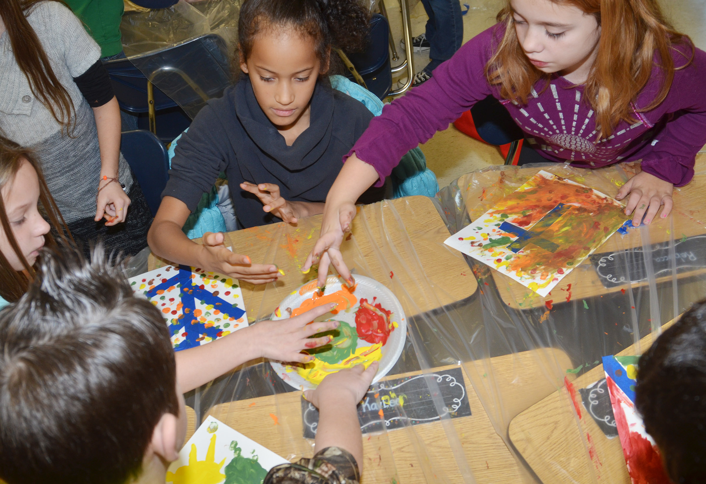 From left, CES third-graders Codey Parks, Alyah Meadows, Yazlyn Sutton and Angelina Babbs paint with their fingers.