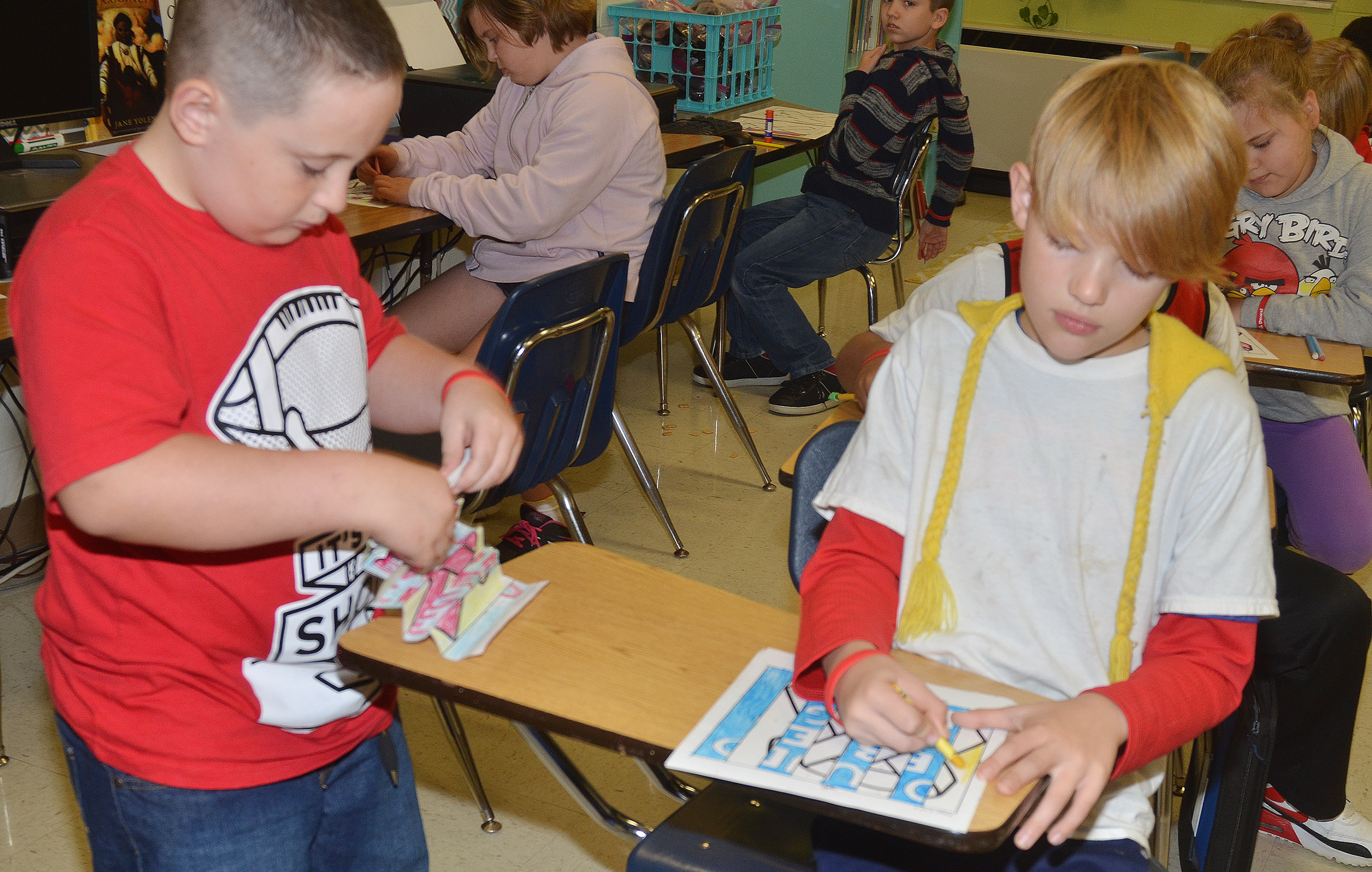 CES fourth-graders J.J. Scharbrough, at left, and Jonathan Releford color and fold their agamographs.