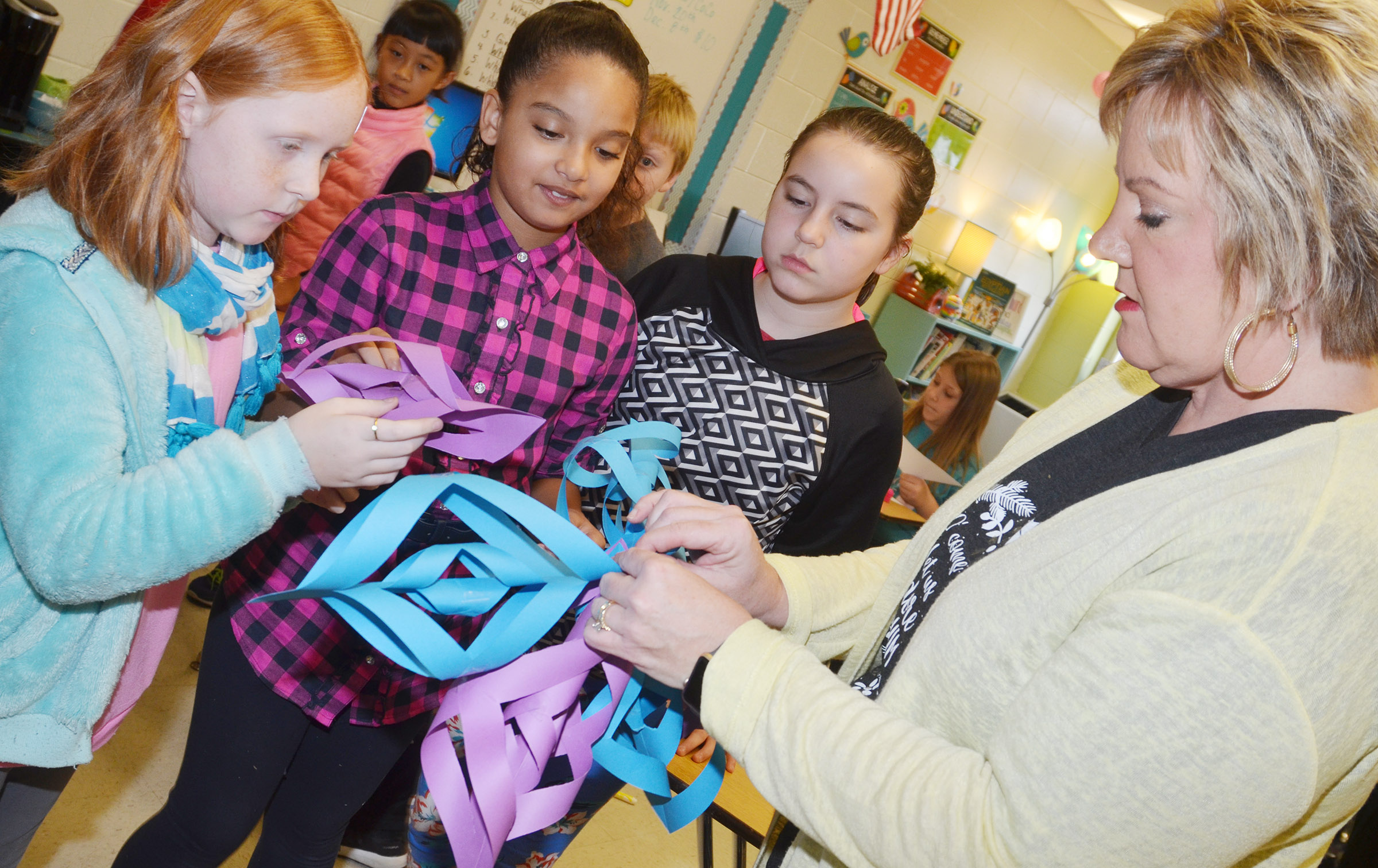 CES fourth-graders, from left, Nora Harris, Aleecia Knezevic and Alexis Roddy make a snowflake with teacher Kaye Agathen.