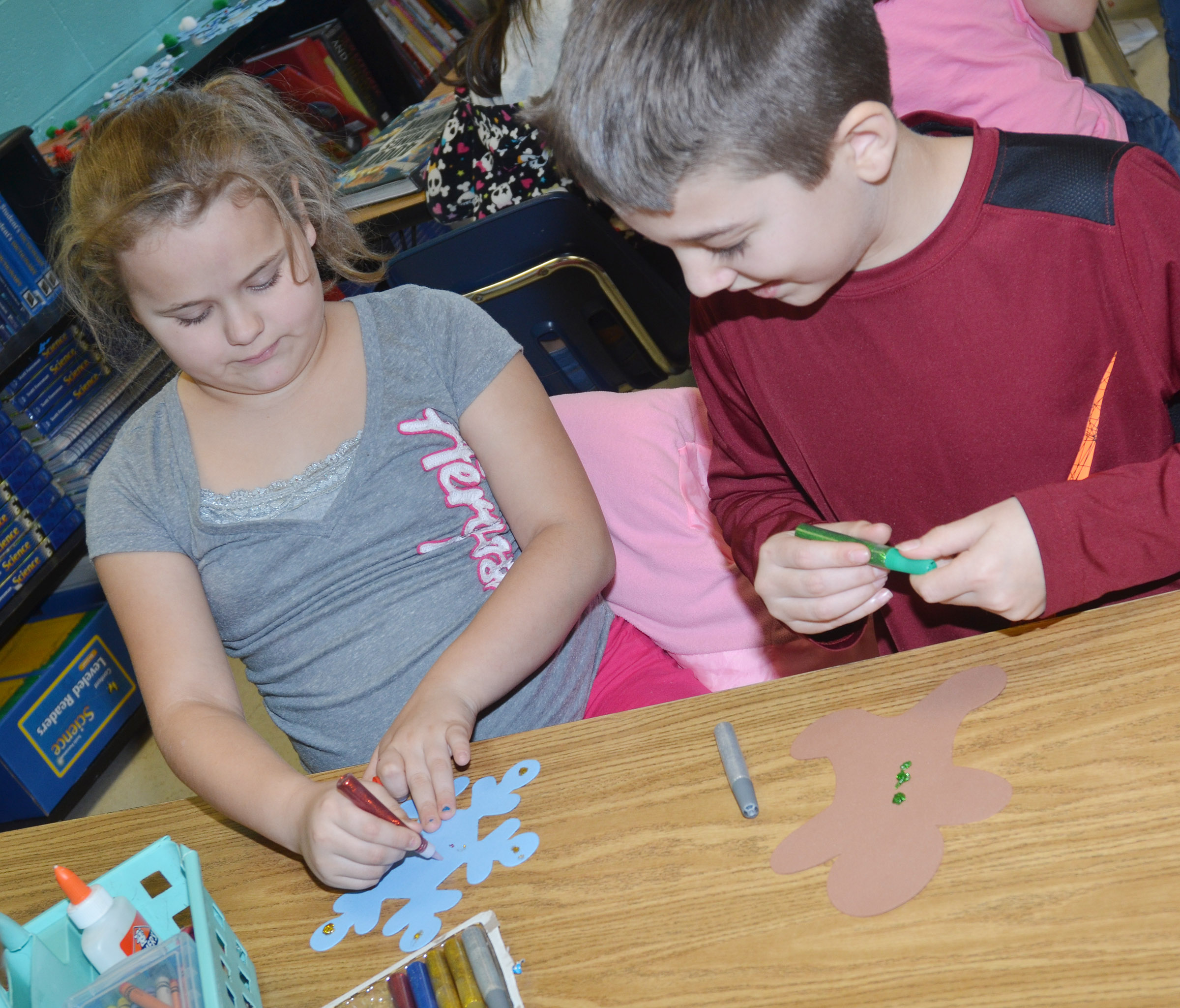 CES fourth-graders Amaya Anguiano, at left, and Landon Tucker make their snowflake and gingerbread men ornaments.