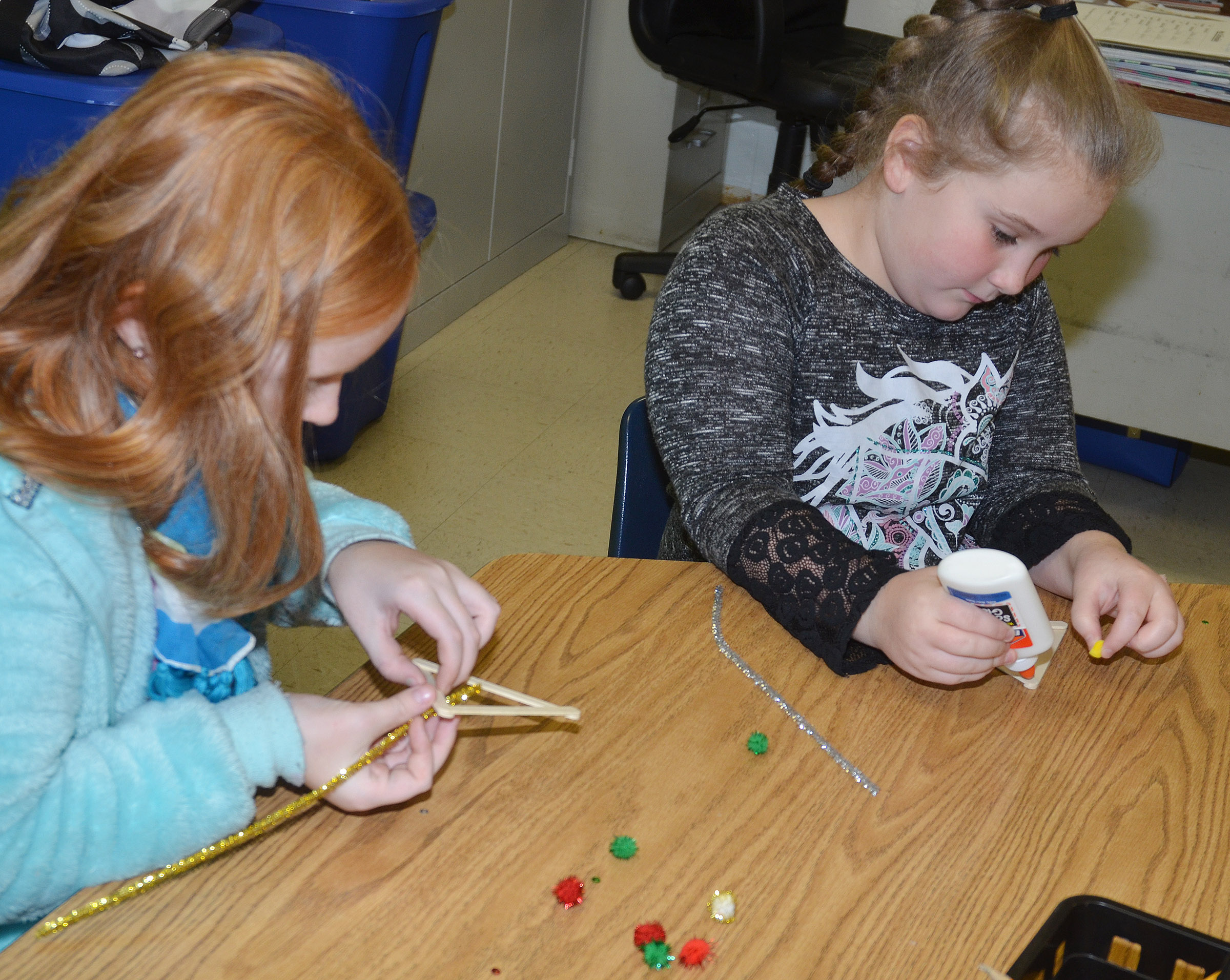 CES fourth-graders Nora Harris, at left, and Kiera Bailey make their ornaments.