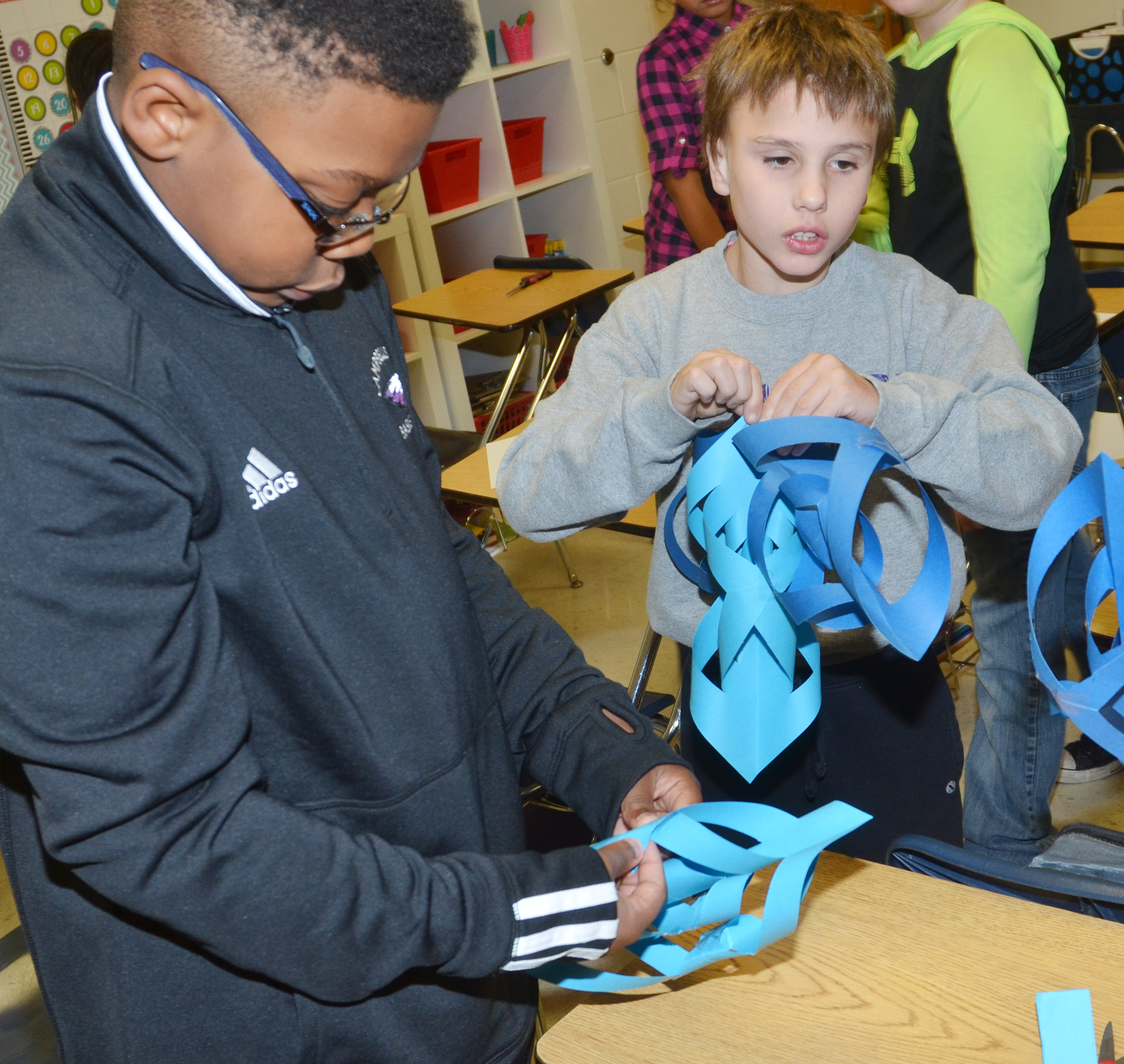 CES fourth-graders Austin Sloan, at left, and Jayden Harris make snowflakes.