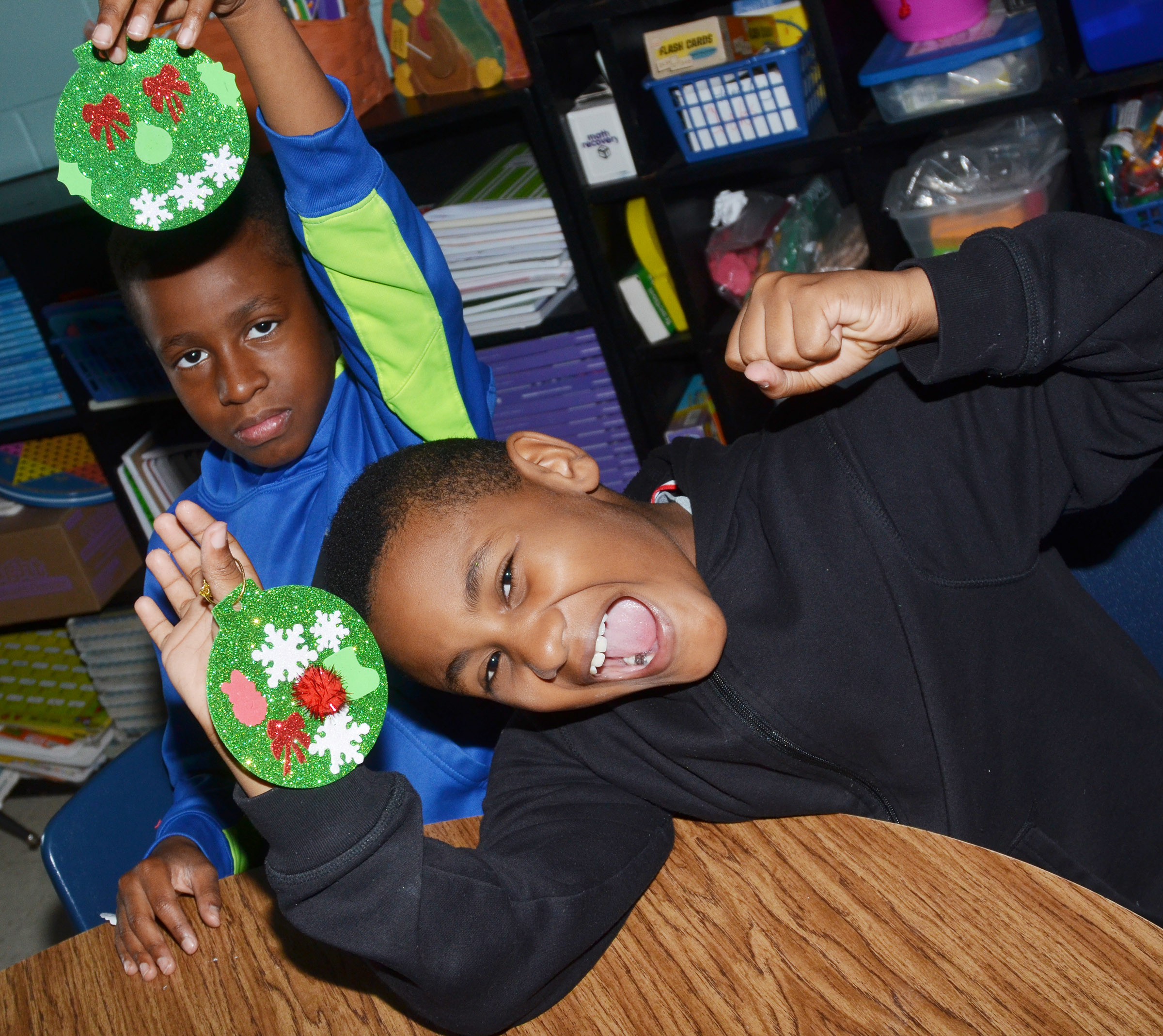 CES fourth-graders John Gholston, at left, and Shaiden Calhoun hold their ornaments.