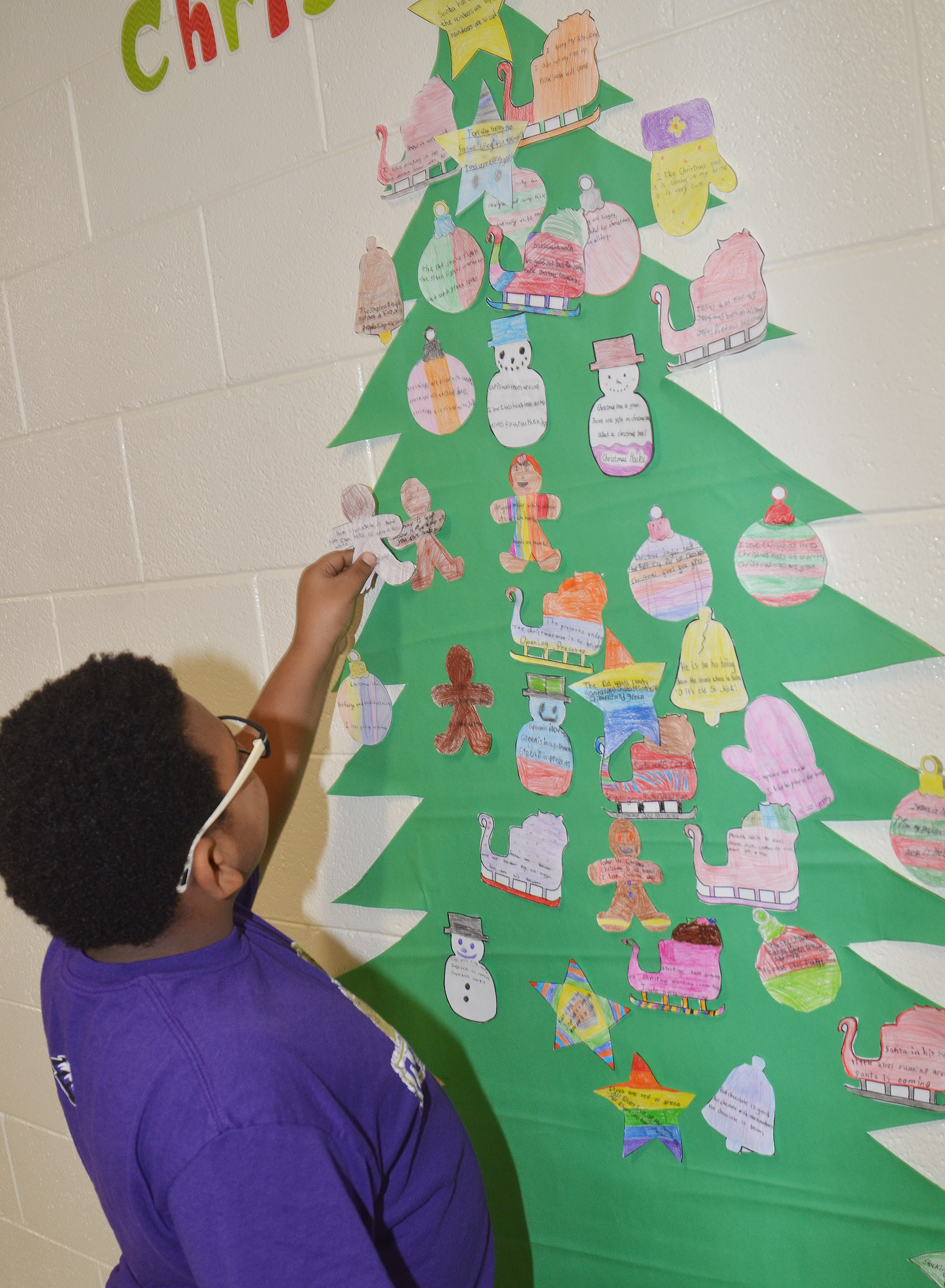 "CES fourth-grader Malikiah Spurling places his ornament on the Christmas ""PoeTree."""