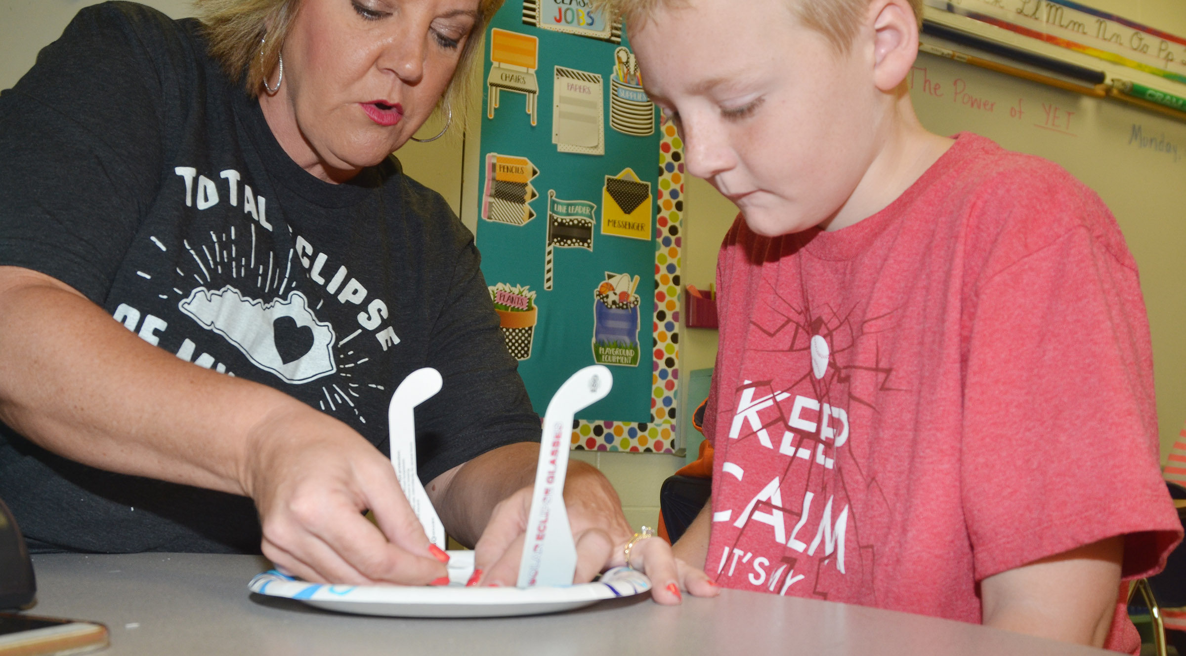 CES fourth-grade teacher Kaye Agathen helps Ryder Murphy make his solar eclipse mask.