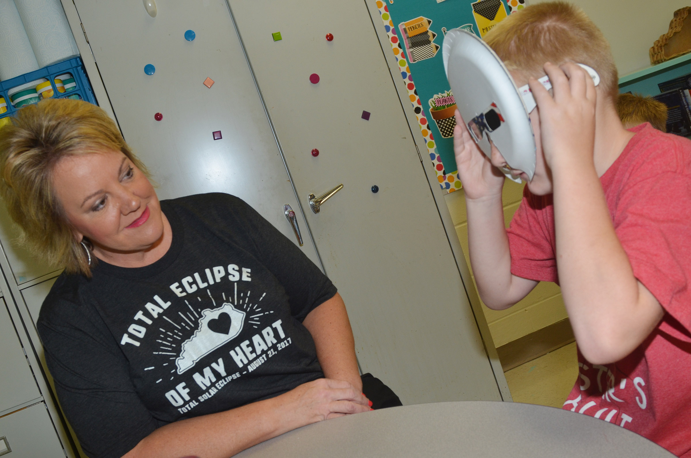 CES fourth-grader Ryder Murphy tries on his solar eclipse mask, as teacher Kaye Agathen watches.