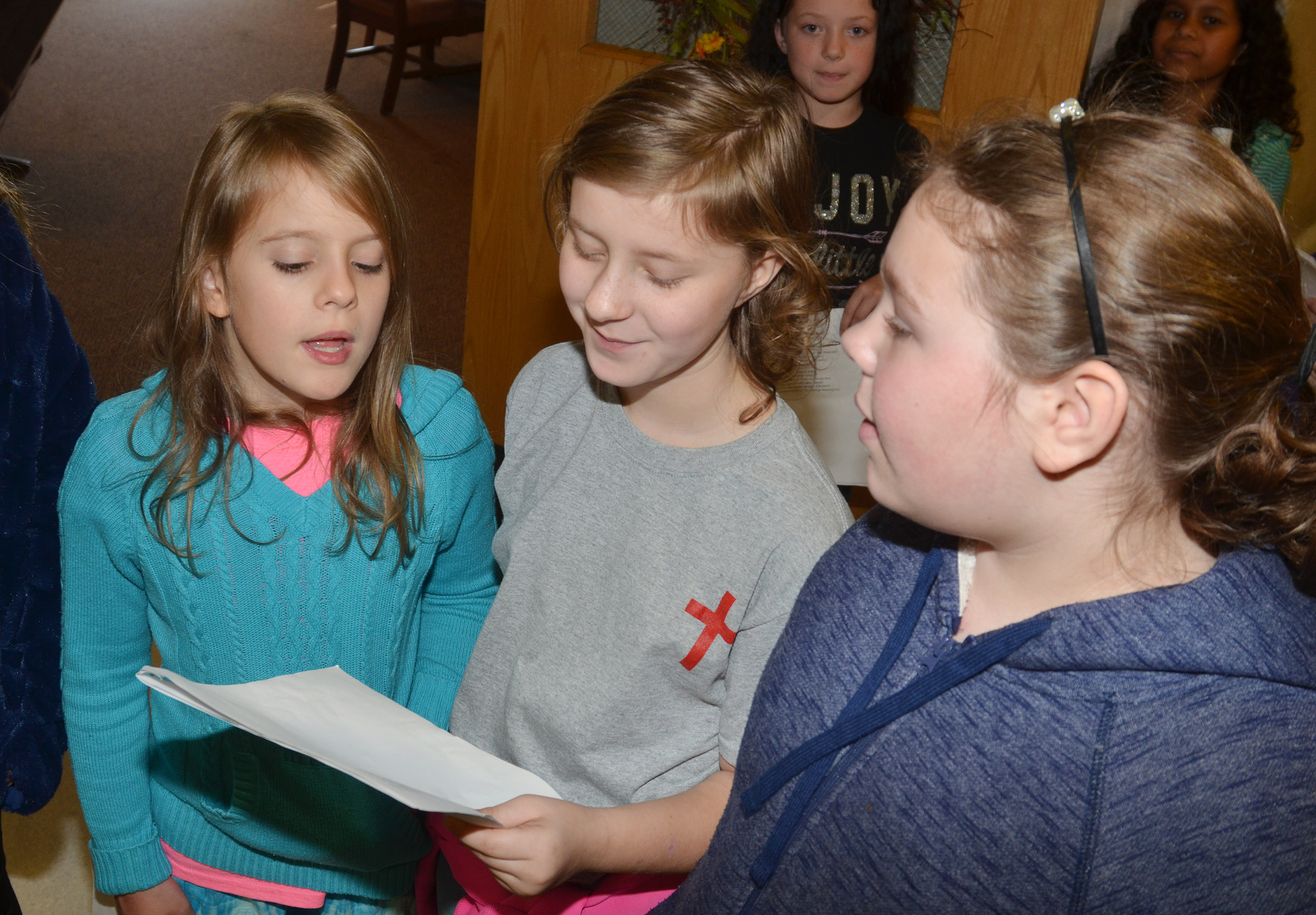 From left, CES fifth-graders Ellie Wise, Bryanna Fitzgerald and Averi Perkins sing a Christmas carol at Grandview.