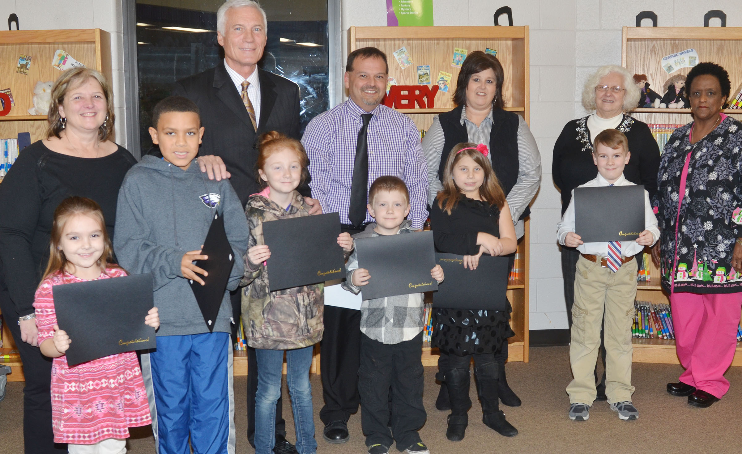 CES students named Academic Achievers for December are pictured with Campbellsville Board of Education members. From left, front, are kindergartener Aubrey Allen, third-graders Christian Hart and Savannah Wethington, kindergartener Gage Henderson and second-graders Natalia West and Stephen Green. Back, Board member Angie Johnson, CIS Superintendent Mike Deaton, CES Principal Ricky Hunt, Board member Suzanne Wilson, Board Chair Pat Hall and Board member Barkley Taylor. Absent from the photo are CES first-graders Asia Singleton and Dax Gray.