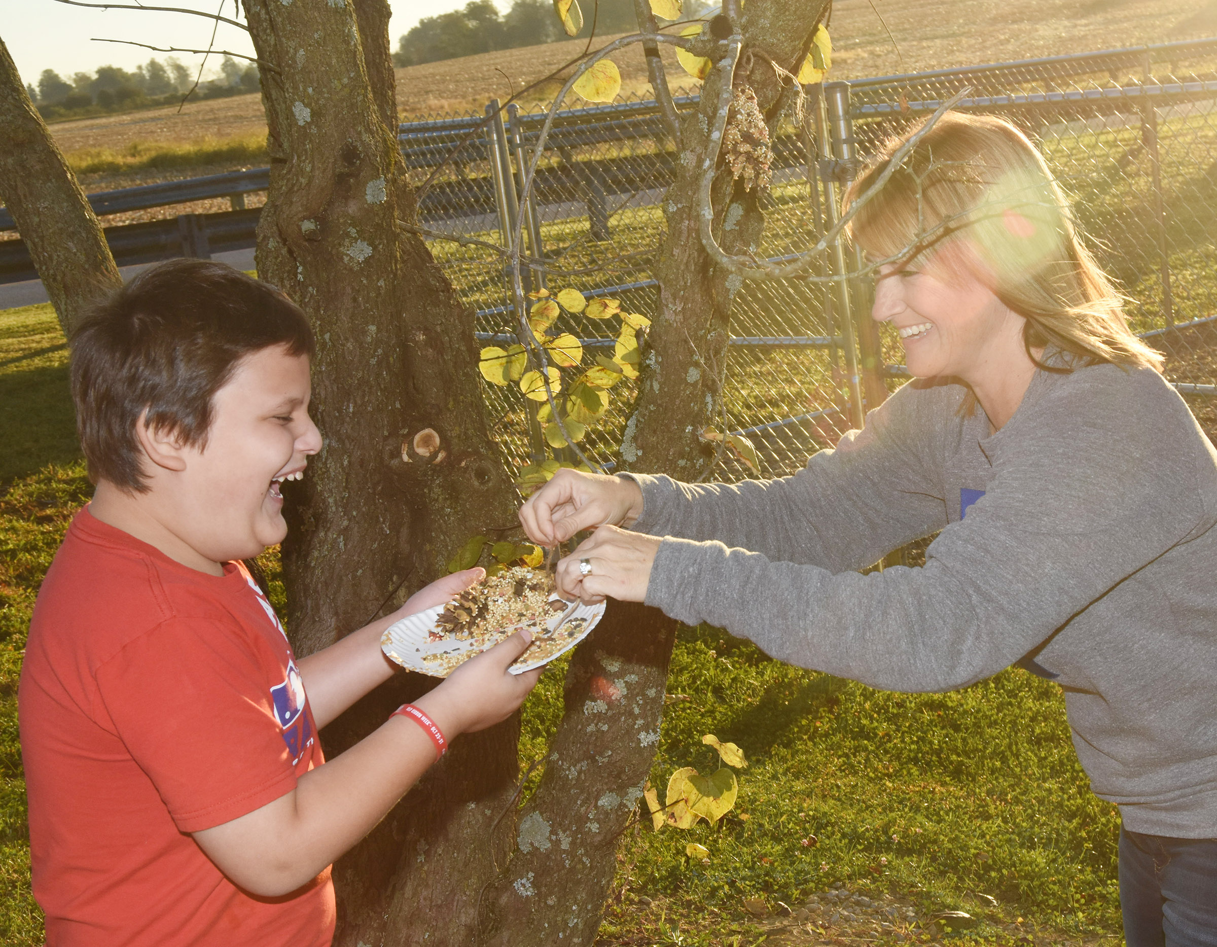 CES second-grader Cloud Malone hangs his bird feeder, with help from teacher Vanessa Adkins.