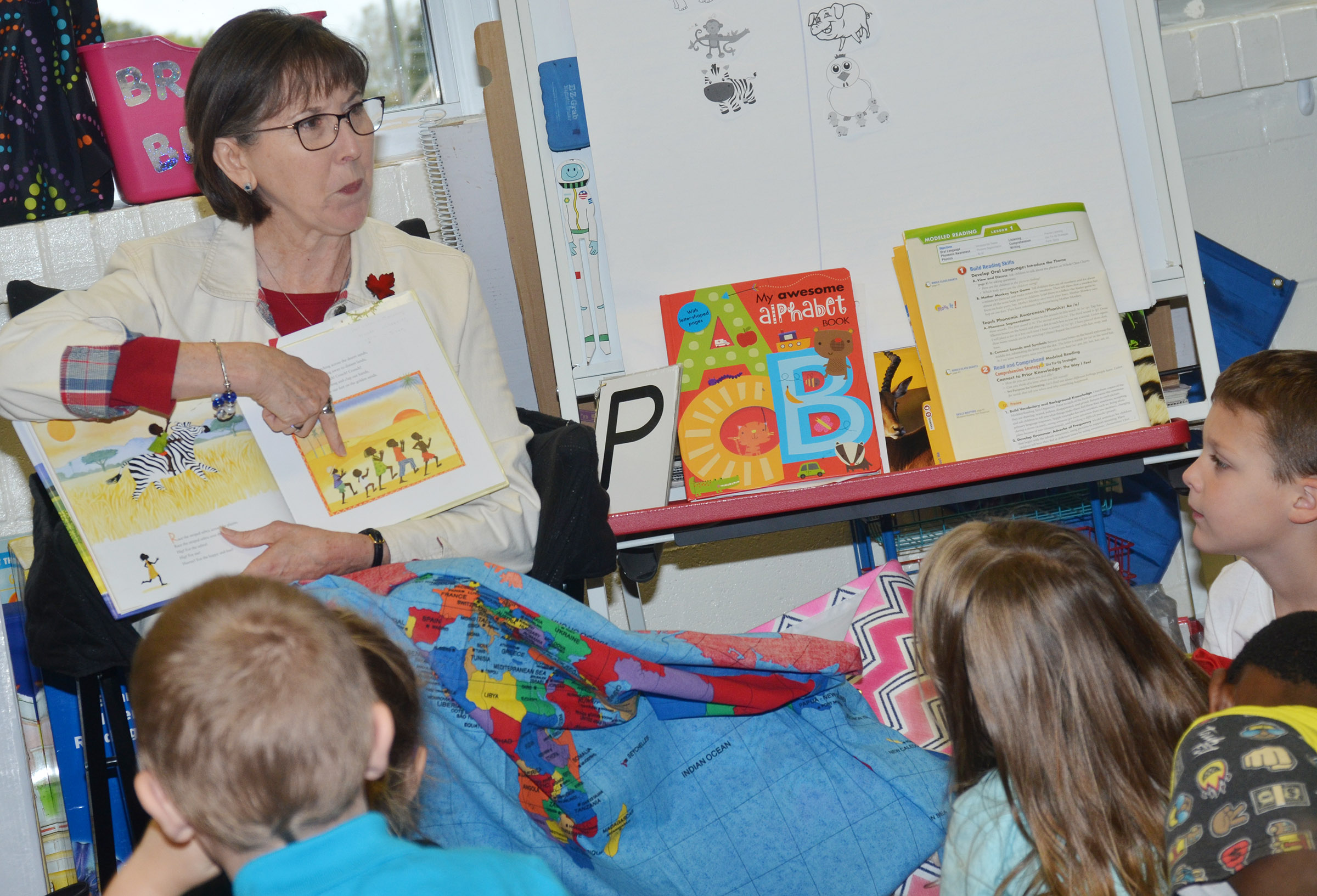 Penny Akers, a retired teacher, reads CES kindergarteners a story about Africa.