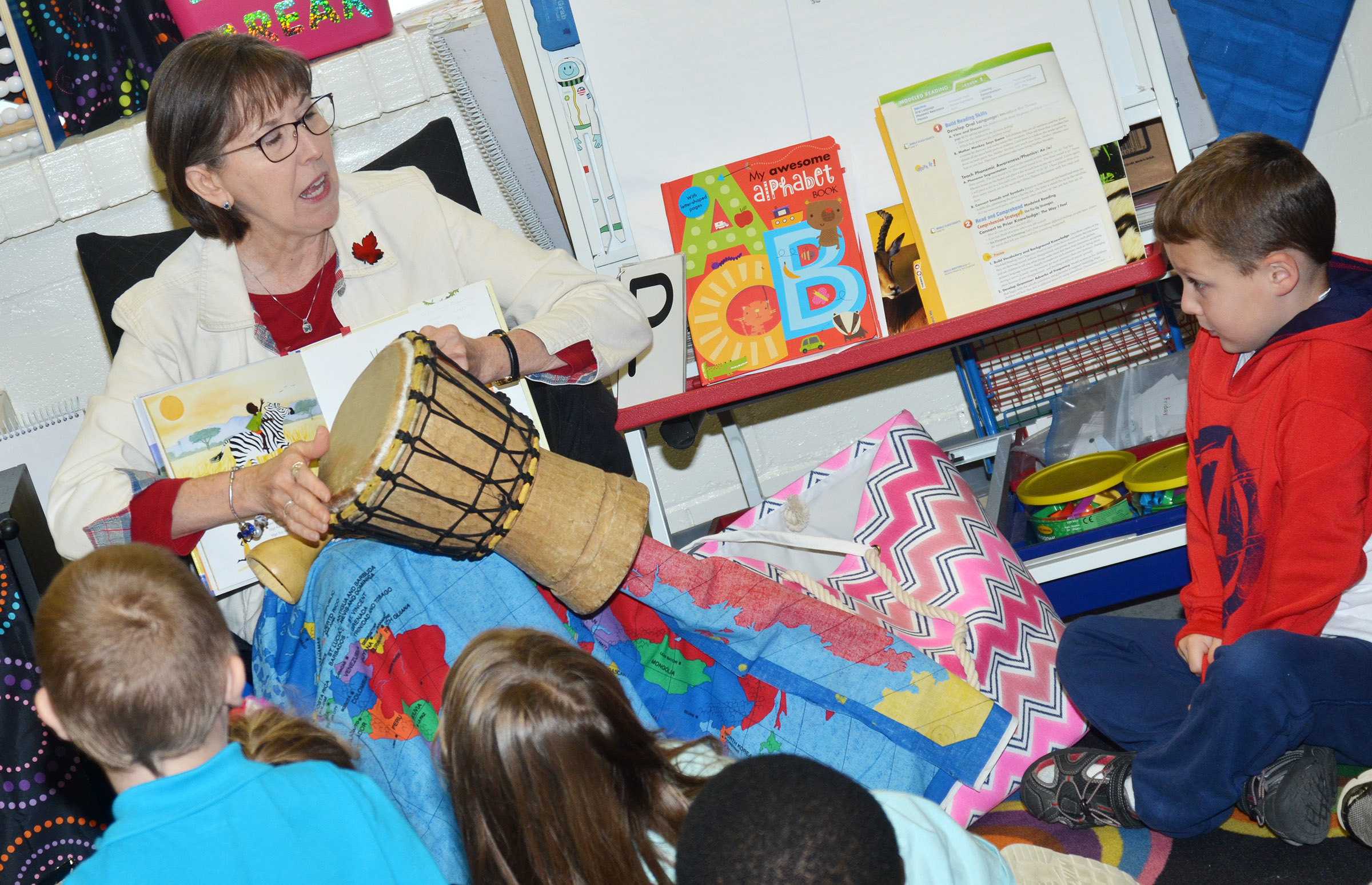 Penny Akers, a retired teacher, shows CES kindergarteners what a djembe looks and sounds like.