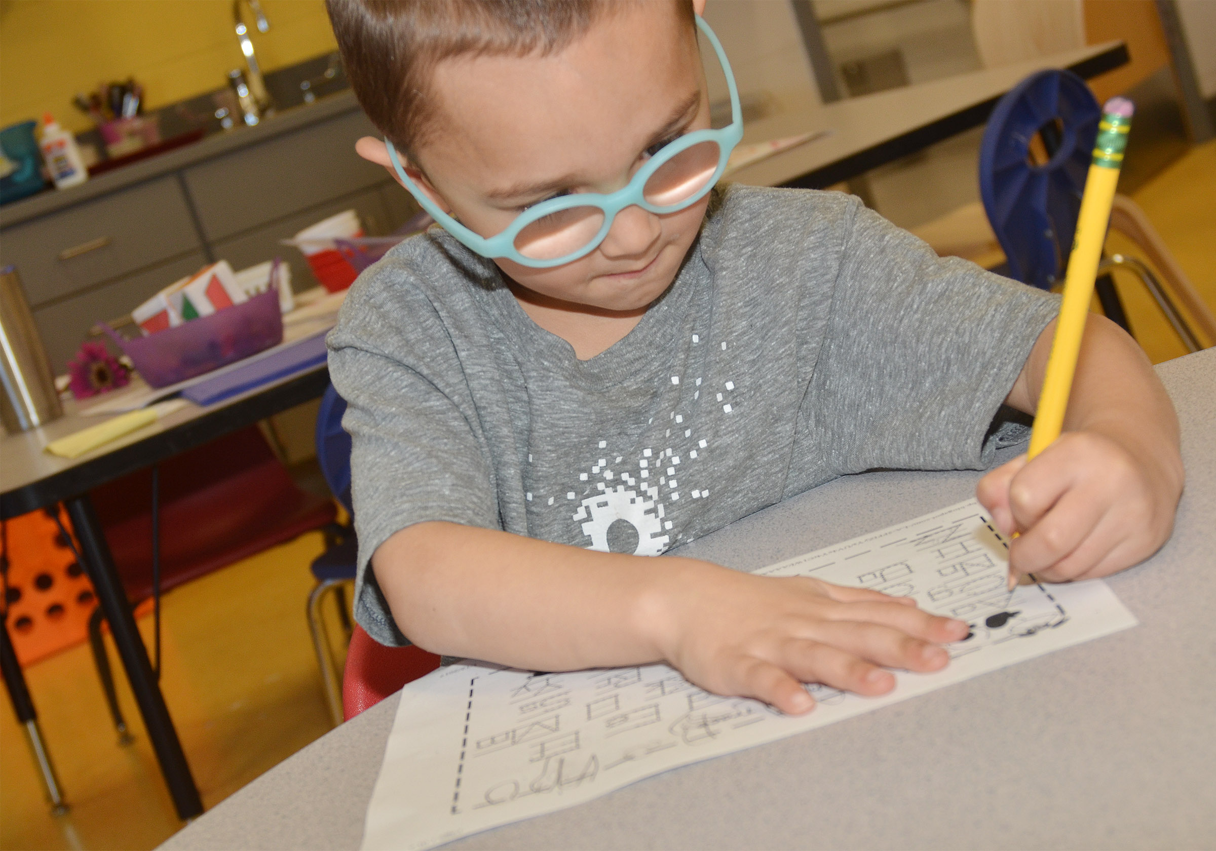 CES preschool student Chanler Mann practices writing the alphabet.
