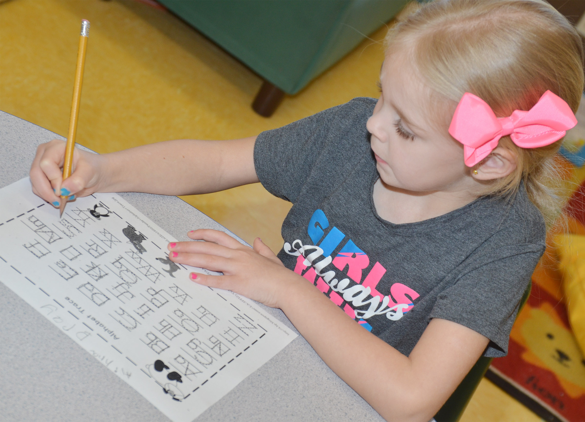 CES preschool student Alinna Bray practices writing the alphabet.