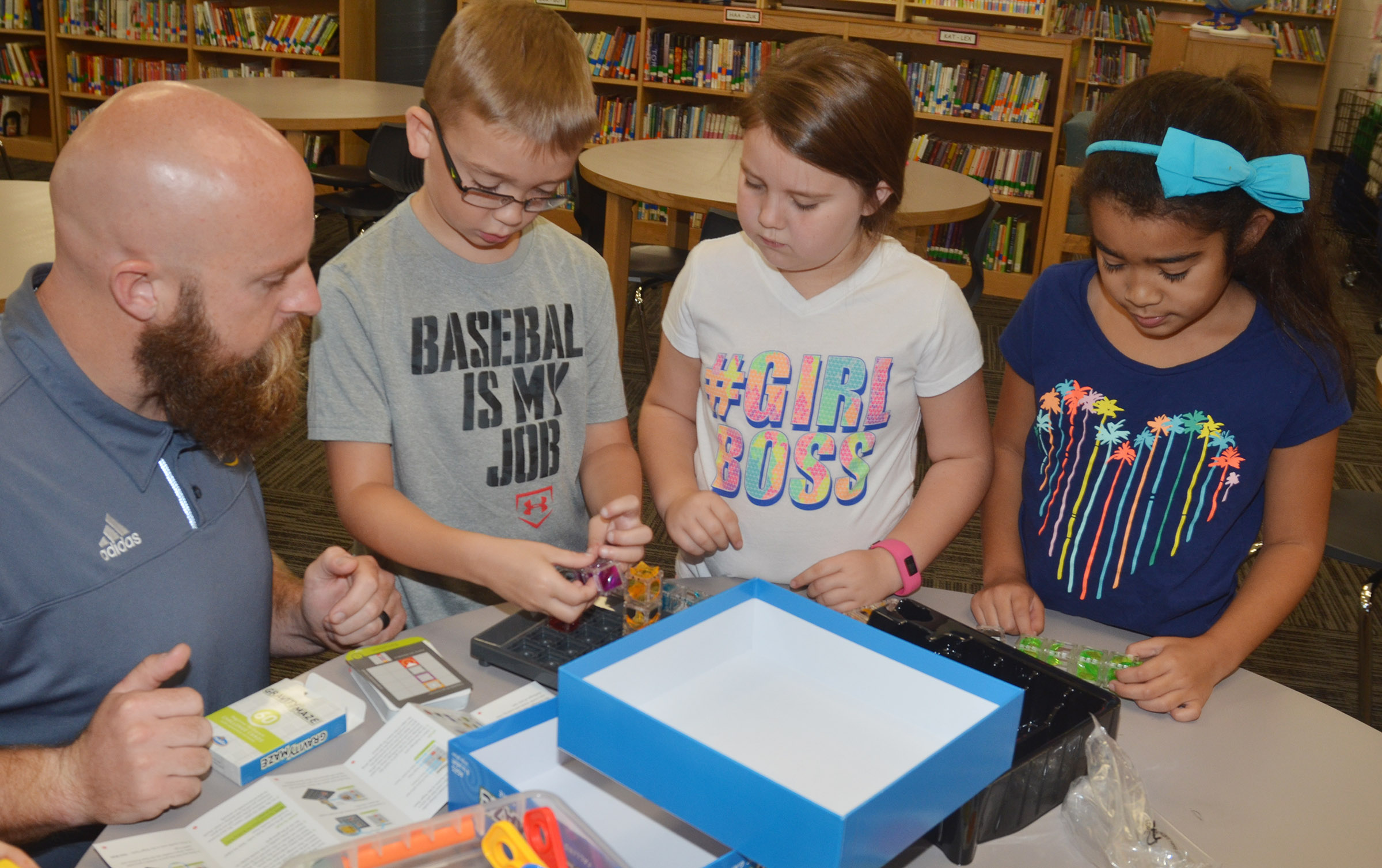 Chad Forsyth, an operations manager at Amazon, plays with STEM toys with, from left, fourth-graders Cameron Estes and Maylee Wilds and third-grader Sophia Santos.