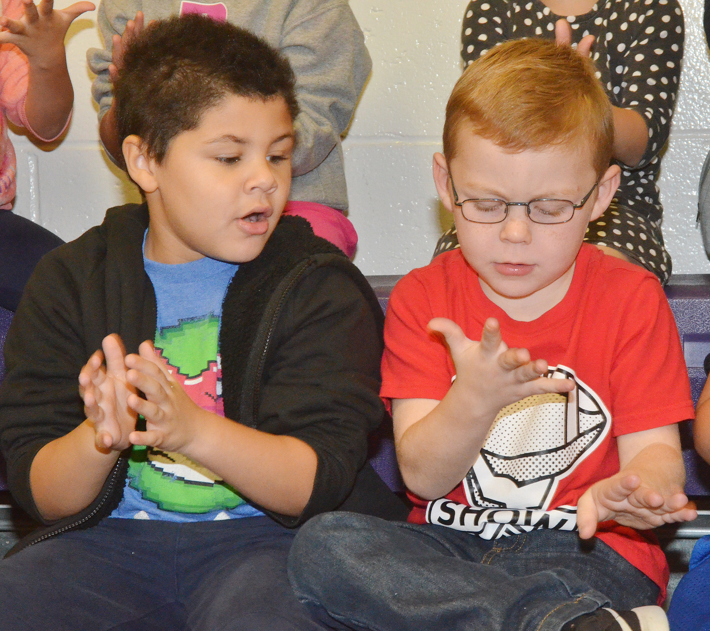"CES first-graders NyJah Vaught, at left, and Daven Davis aren't quite sure about the ""germs"" that have been placed on their hands."
