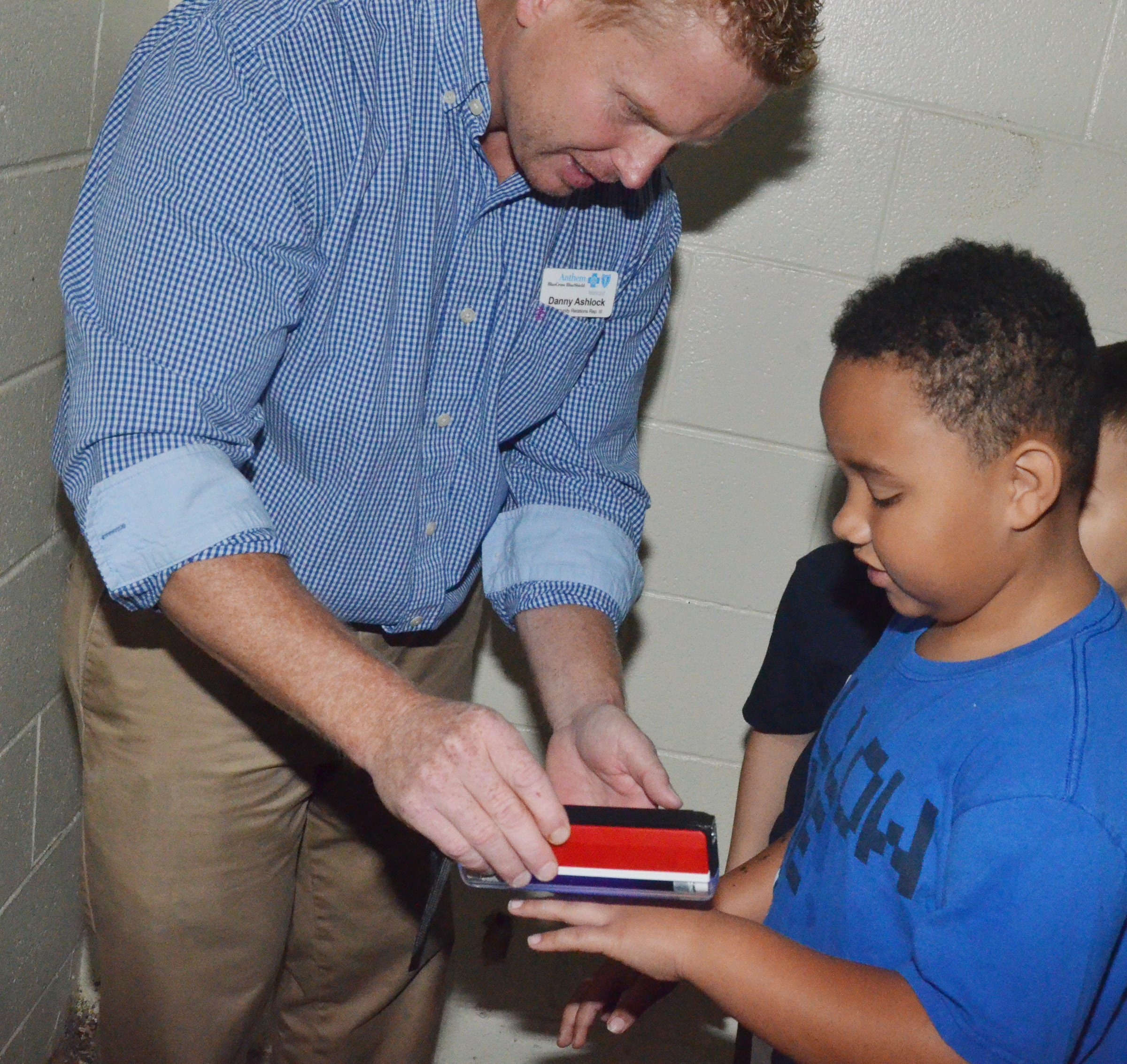Danny Ashlock, a representative from the Anthem insurance company, sees how well first-grader Justin Walls washed his hands.
