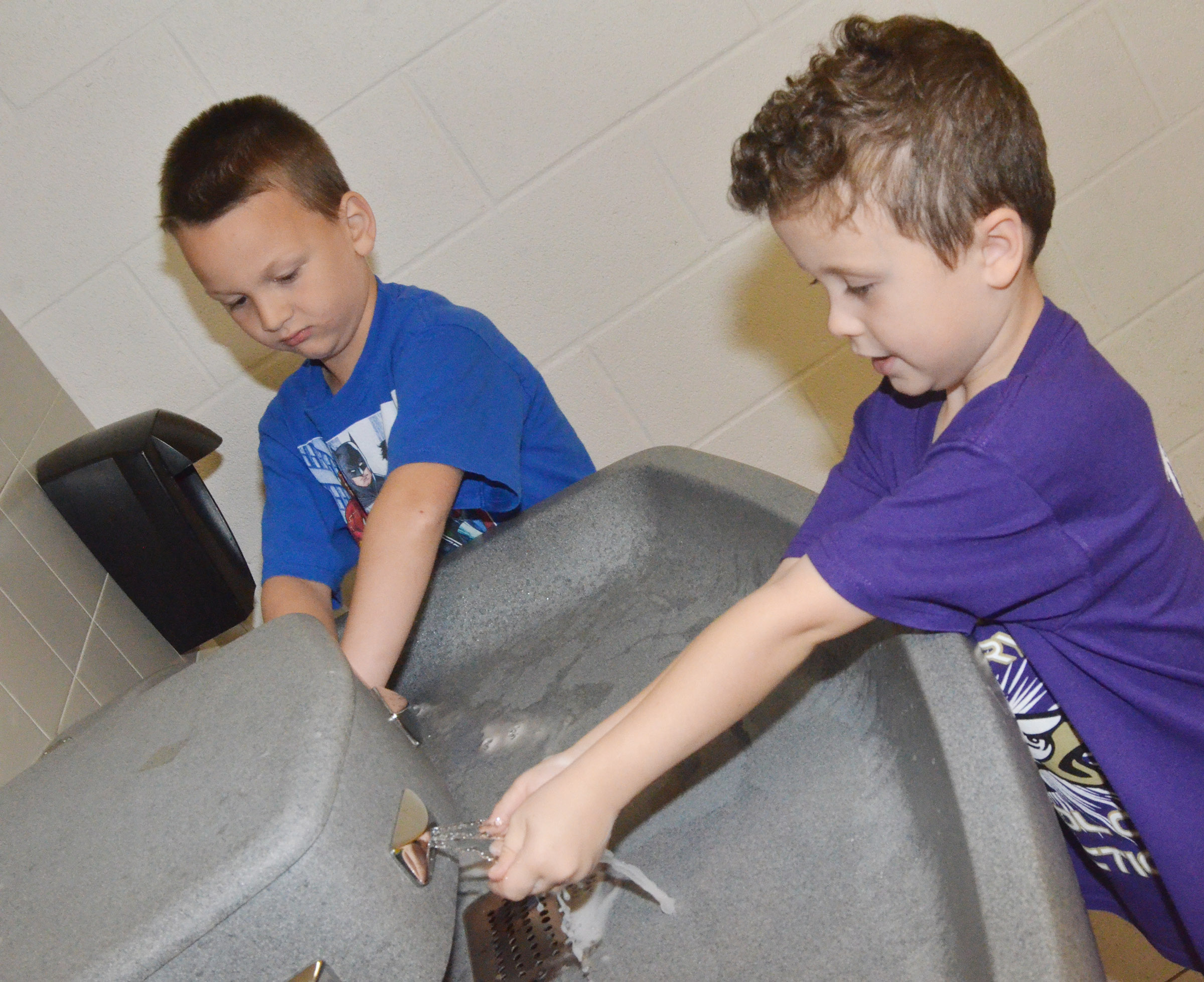 CES first-graders Justice Nelson, at left, and Braydan Dyer practice washing their hands.