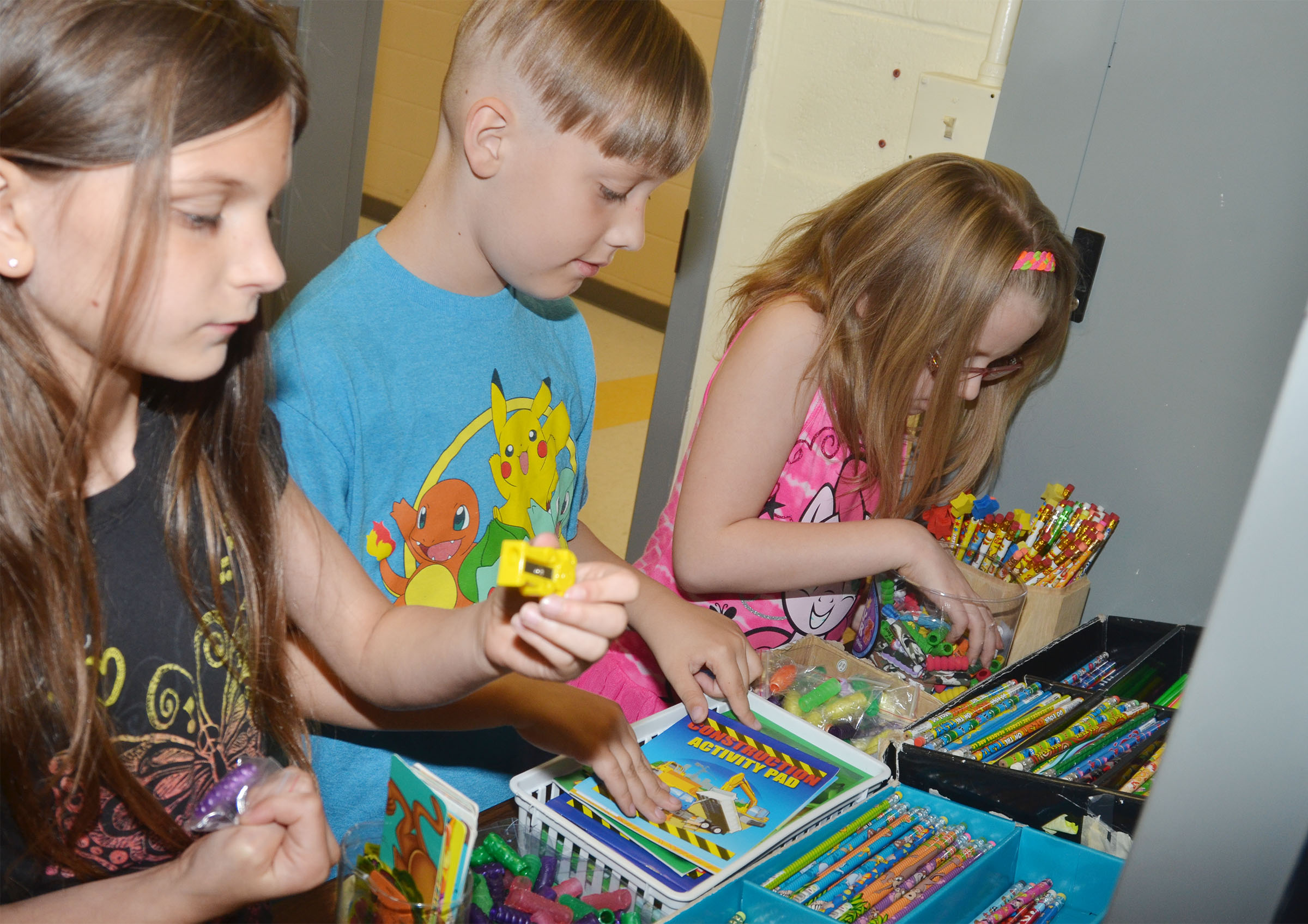 From left, CES third-graders Madie Gebler, Izak Burress and Gracie Pendleton shop with their AR points.