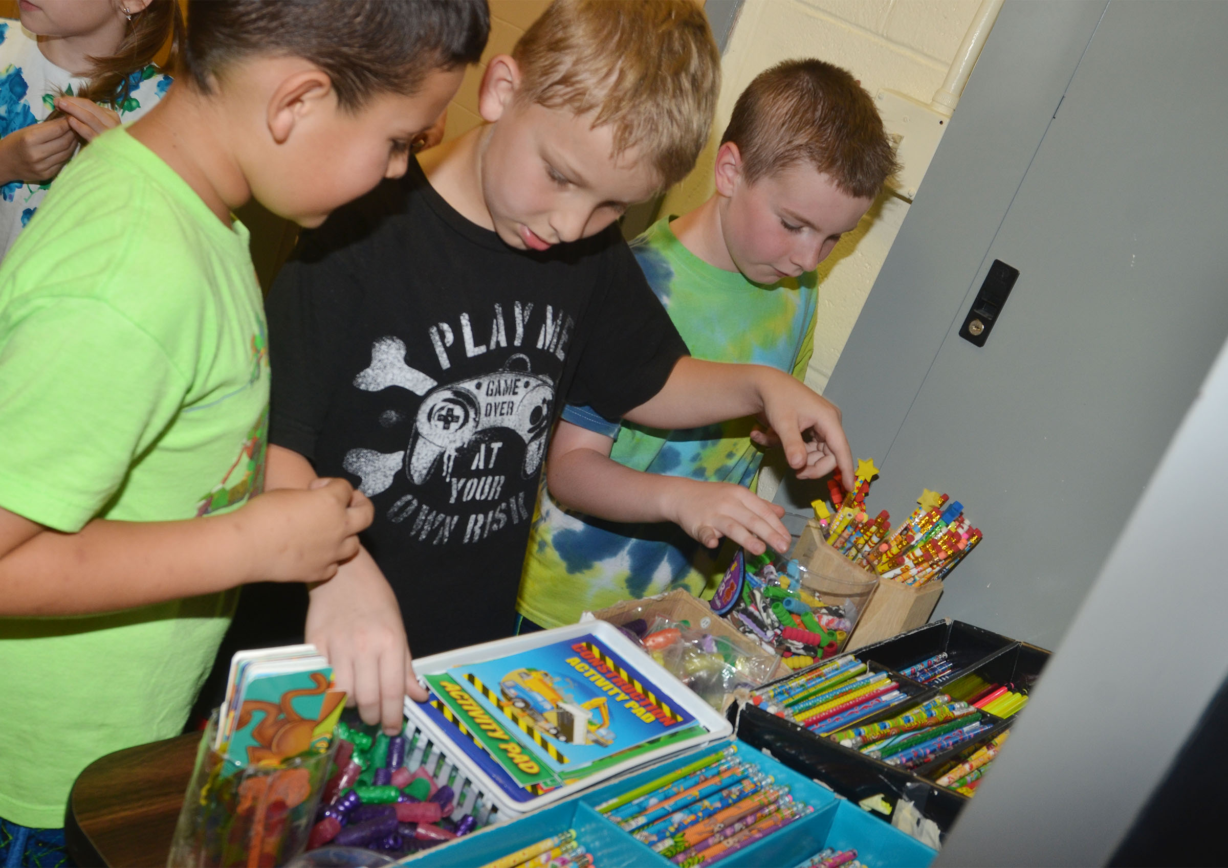 CES second-graders, from left, Damien Clark, Mason Davis and Stephen Green shop with their AR points.