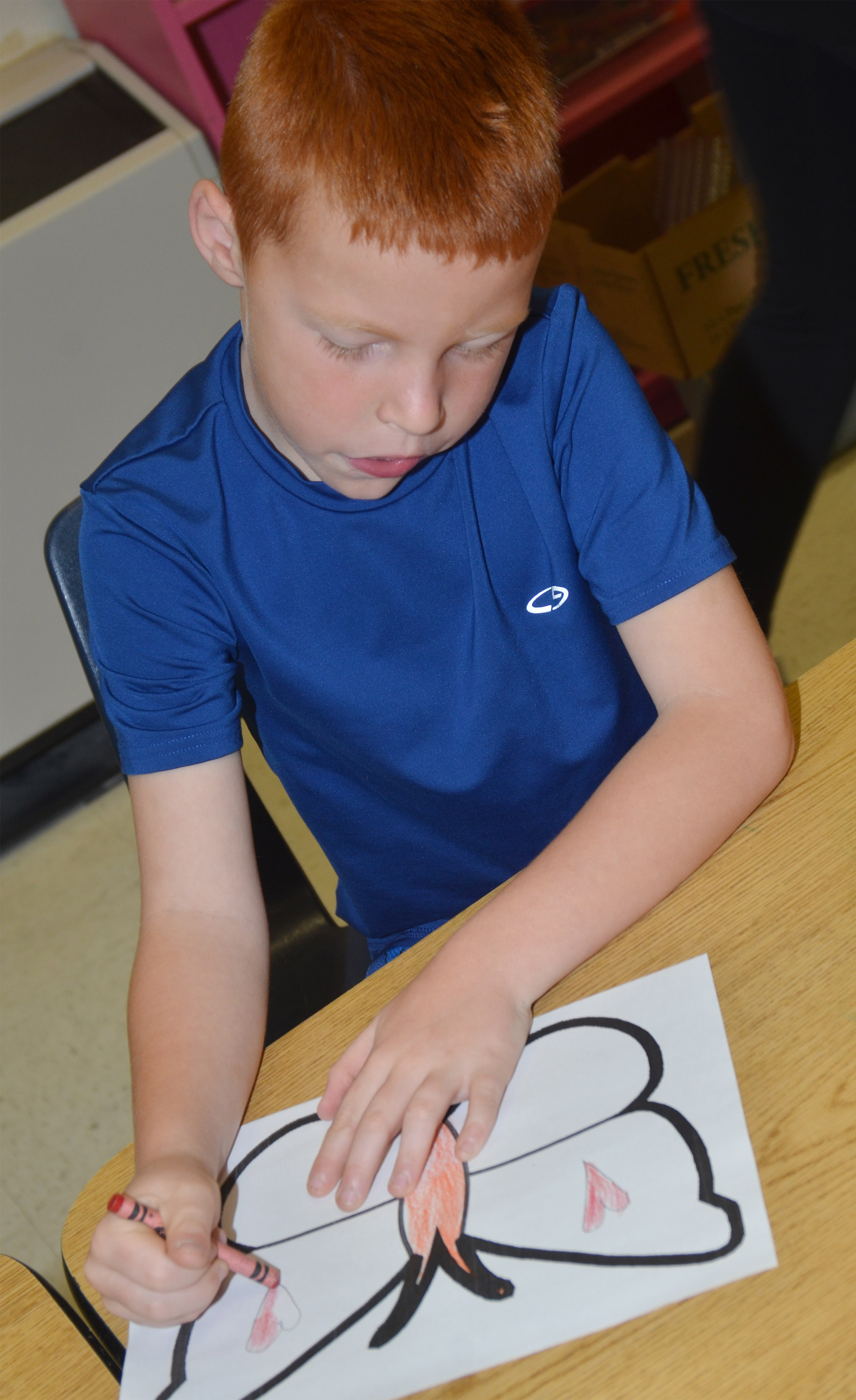 CES first-grader Carter Wethington creates symmetry as he colors his butterfly.