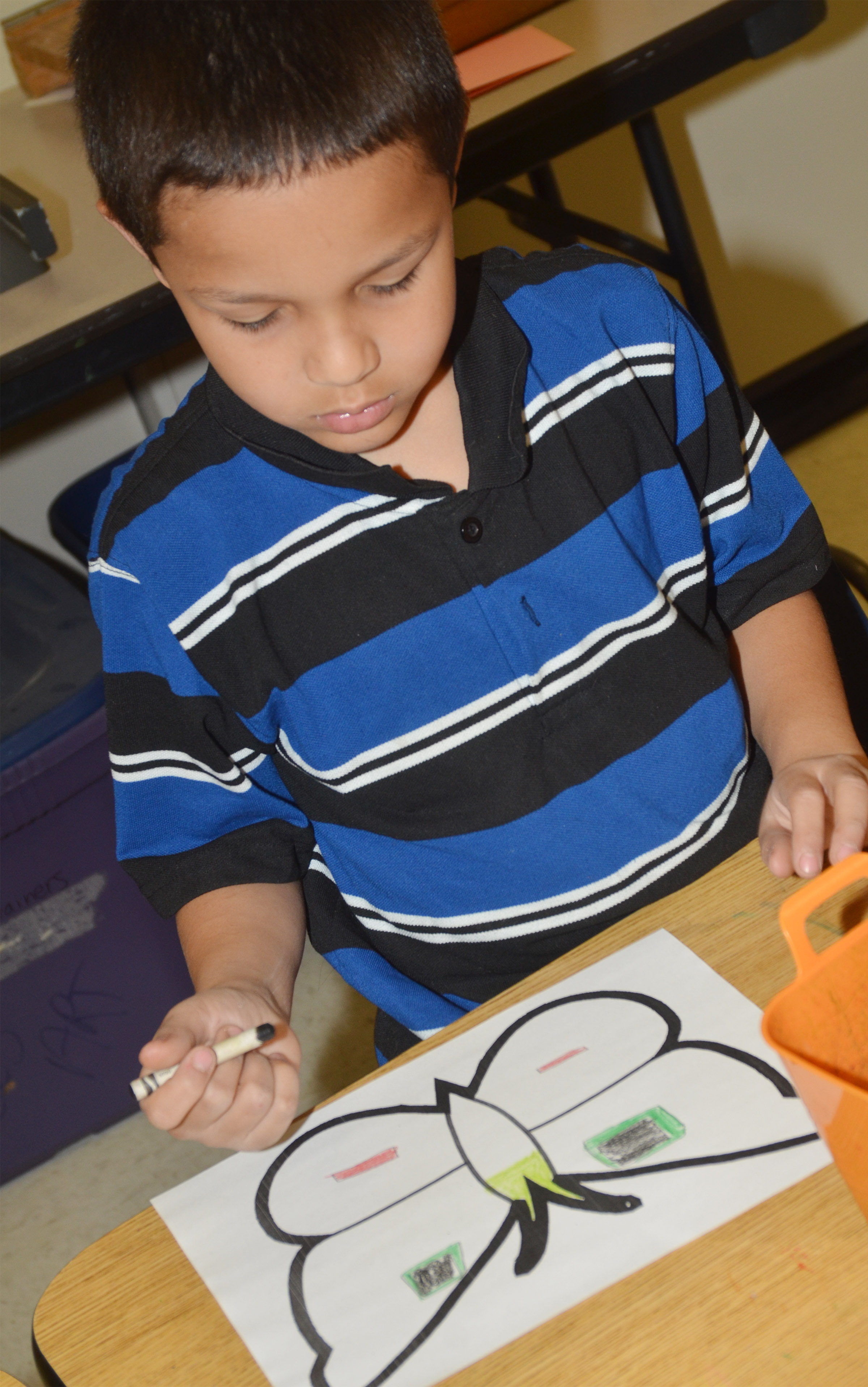 CES first-grader Makyian Bridgewater creates symmetry as he colors his butterfly.
