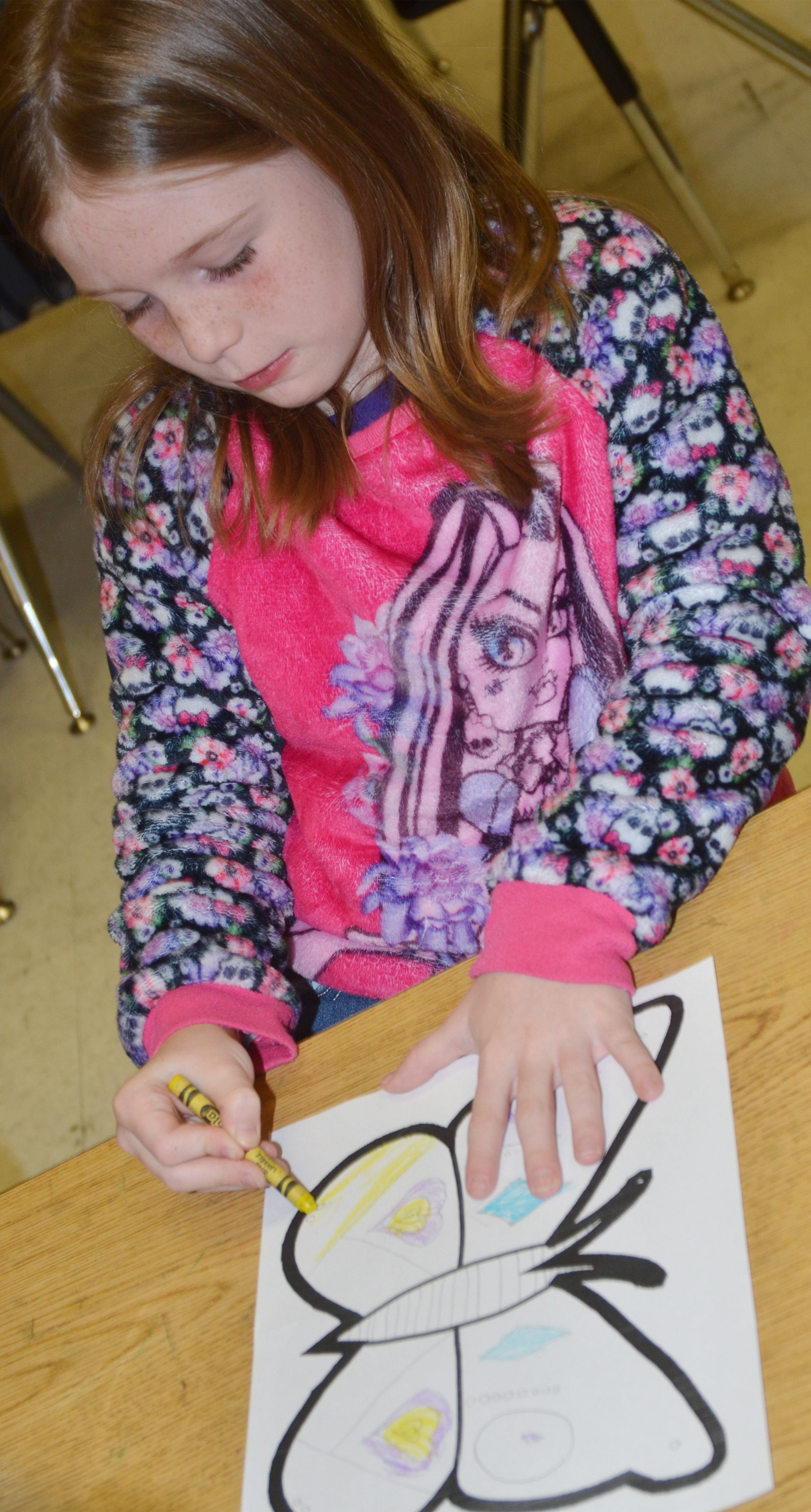 CES first-grader Izzy Brunelle creates symmetry as she colors her butterfly.