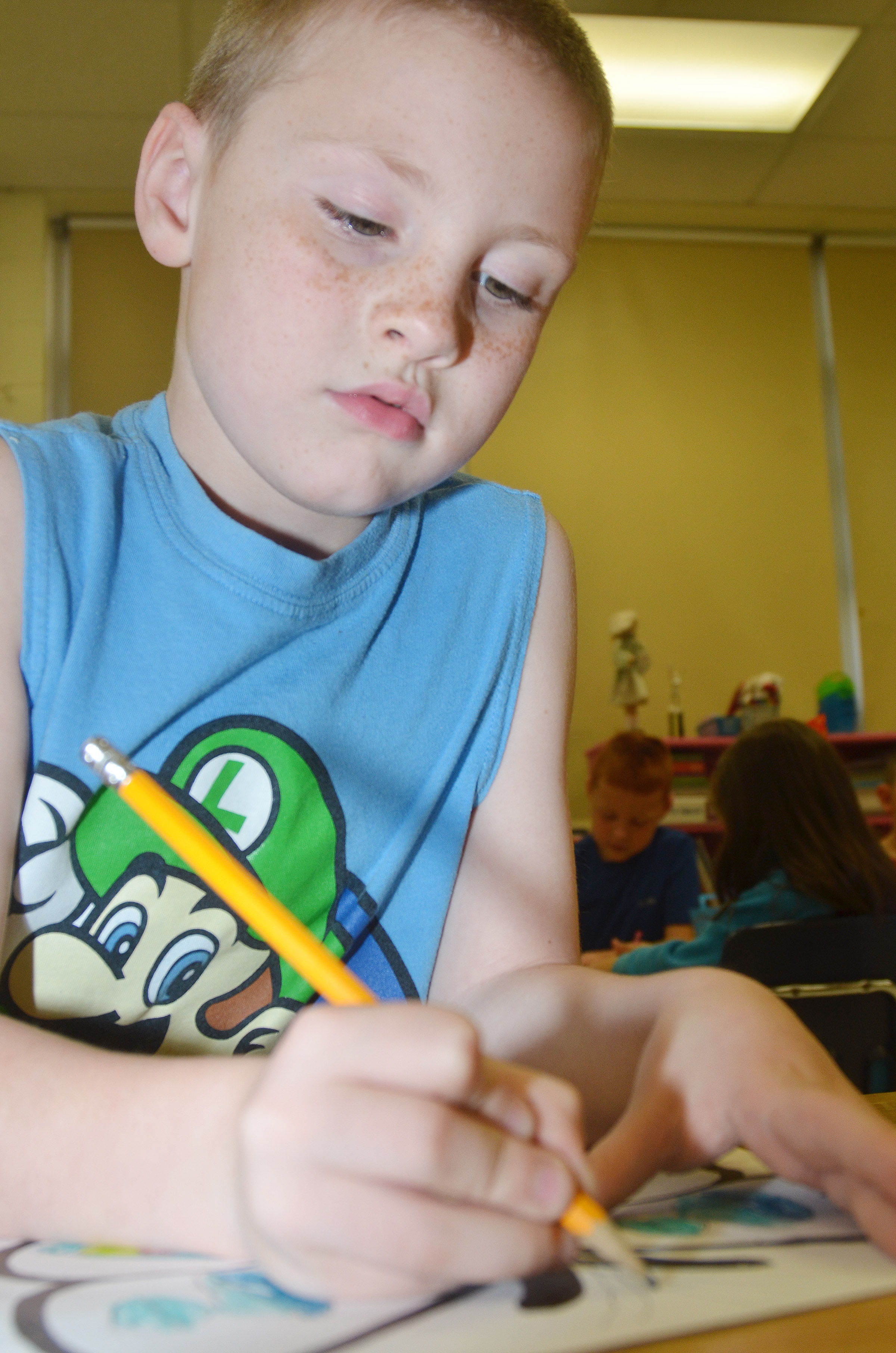 CES first-grader James Brunner creates symmetry as he colors his butterfly.