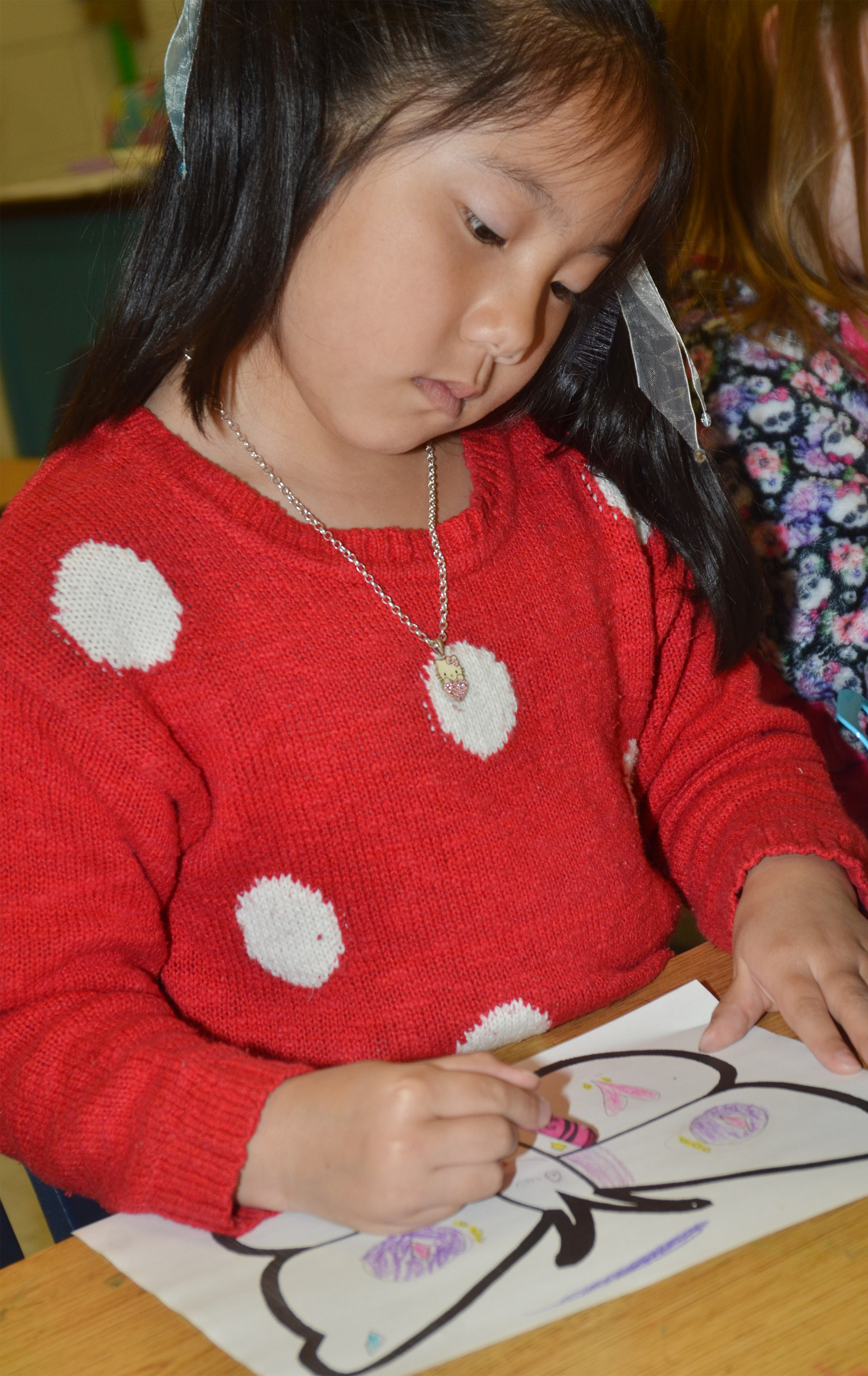 CES first-grader Tina Jiang creates symmetry as she colors her butterfly.