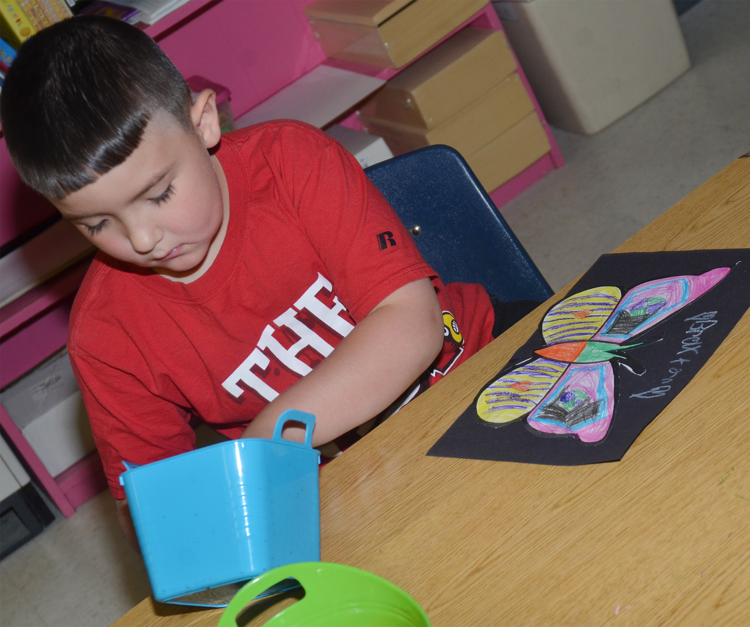 CES first-grader Braxton Giles-Osinger creates emphasis as he glues his butterfly to black construction paper.